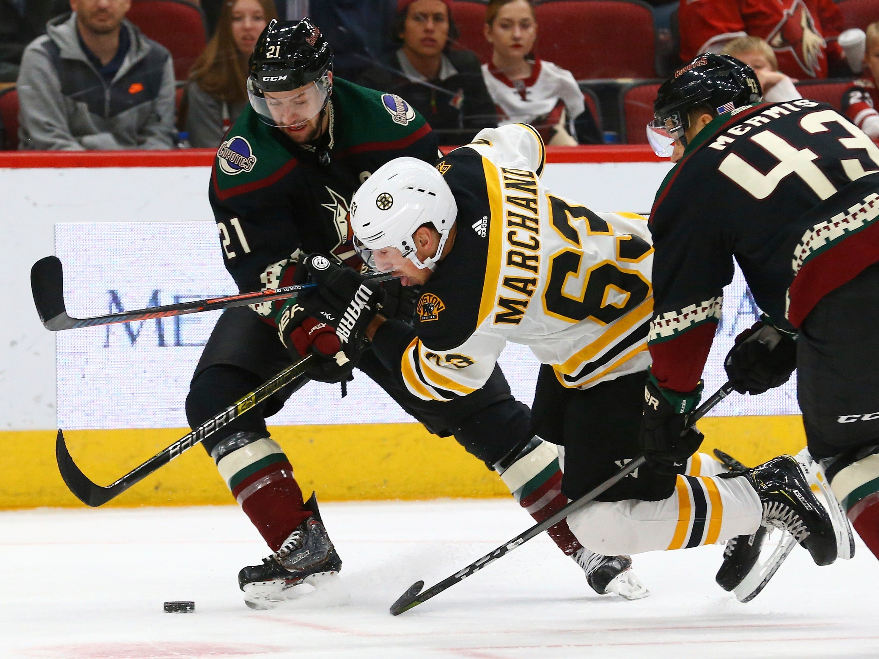 Boston Bruins left wing Brad Marchand (63) gets tripped up by Arizona Coyotes center Derek Stepan (21) and defenseman Dakota Mermis (43) during the third period of an NHL hockey game Saturday, Nov. 17, 2018, in Glendale, Ariz. The Bruins won 2-1. (AP Photo/Ross D. Franklin)