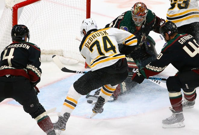 Boston Bruins left wing Jake DeBrusk (74) scores past Arizona Coyotes goaltender Darcy Kuemper, top, right wing Michael Grabner, right, and defenseman Niklas Hjalmarsson (4) during the first period of an NHL hockey game Saturday, Nov. 17, 2018, in Glendale, Ariz. (AP Photo/Ross D. Franklin)