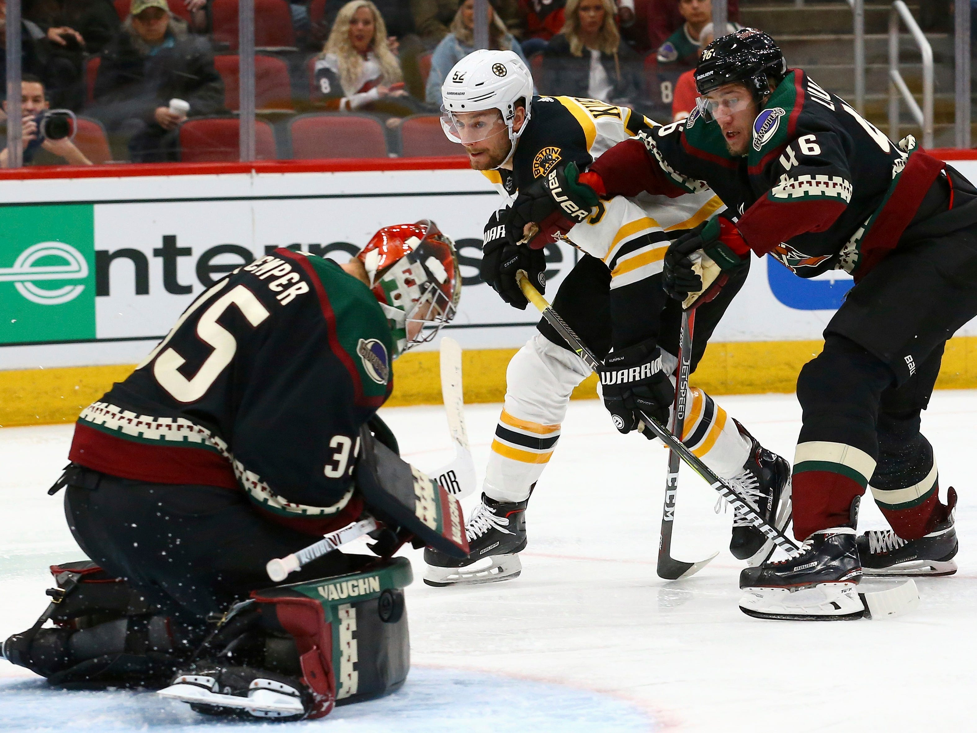 Arizona Coyotes goaltender Darcy Kuemper (35) makes a save on a shot by Boston Bruins center Sean Kuraly (52) as Coyotes defenseman Ilya Lyubushkin (46) watches during the third period of an NHL hockey game Saturday, Nov. 17, 2018, in Glendale, Ariz. The Bruins won 2-1. (AP Photo/Ross D. Franklin)
