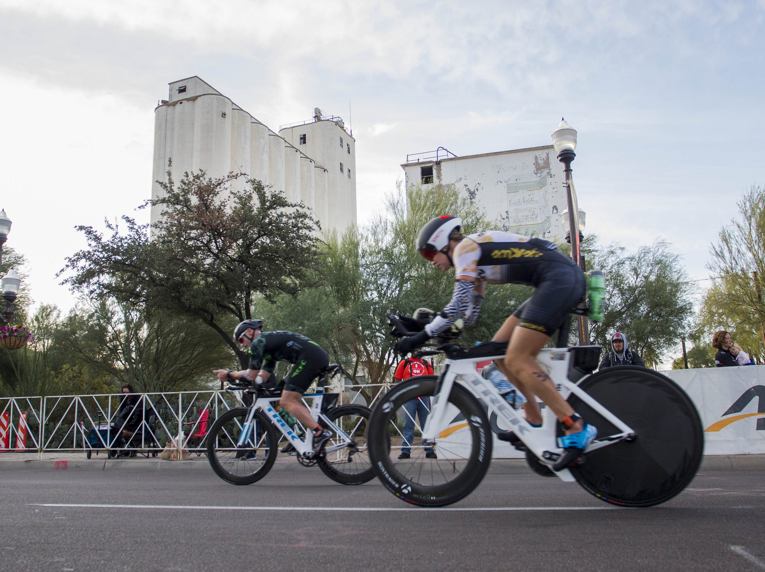 Ironman competitors ride by the old Hayden Flour Mill at the start of the bike portion of the race during the Tempe Ironman at Tempe Town Lake Nov.18, 2018.