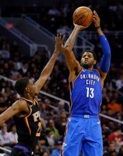 Oklahoma City Thunder forward Paul George (13) shoots over Phoenix Suns forward Josh Jackson during the second half of an NBA basketball game Saturday, Nov. 17, 2018, in Phoenix. Oklahoma City won 110-100. (AP Photo/Rick Scuteri)