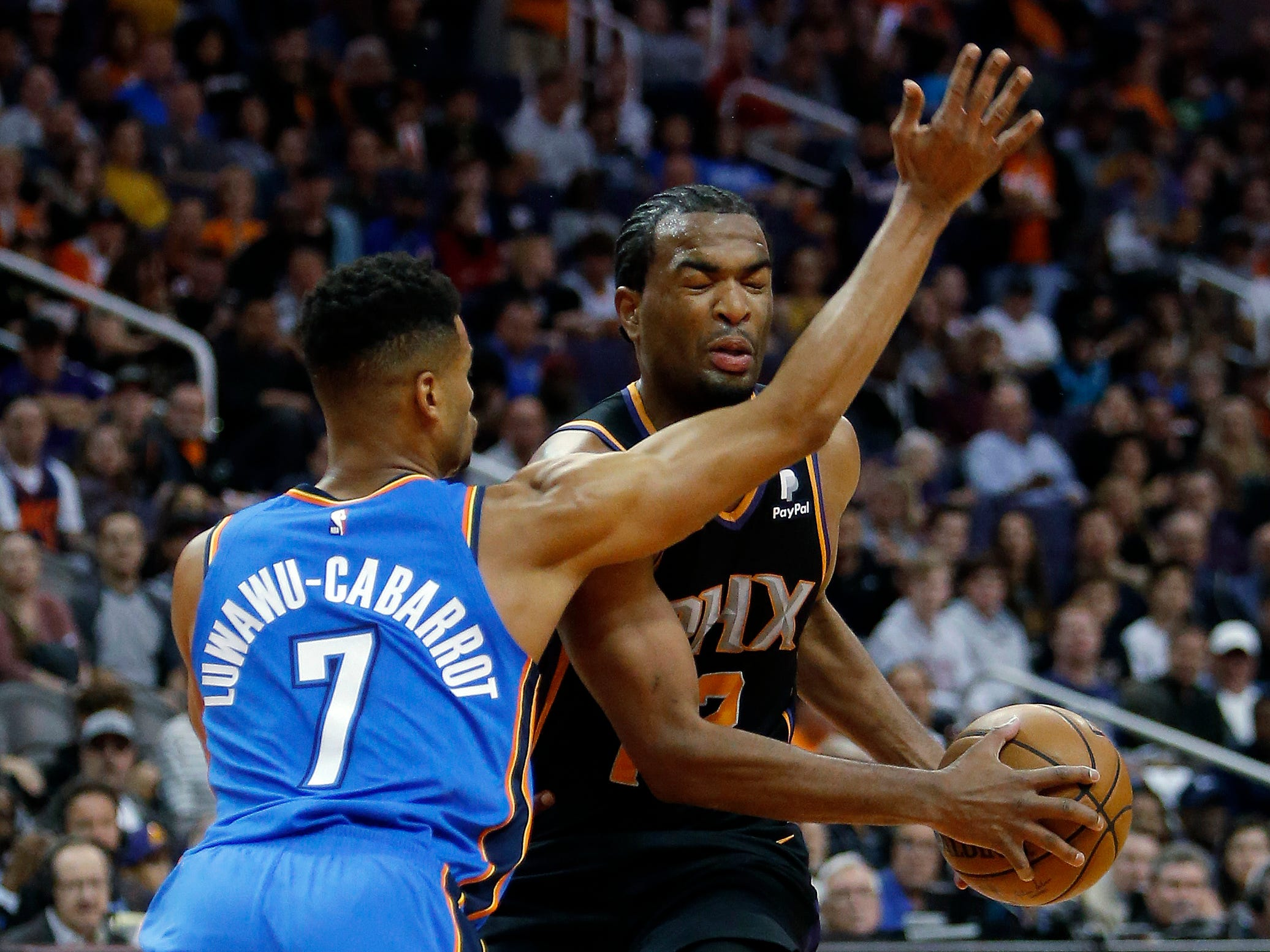 Phoenix Suns forward TJ Warren gets hit in the face by Oklahoma City Thunder guard Timothe Luwawu-Cabarrot (7) on a drive to the basket during the first half of an NBA basketball game Saturday, Nov. 17, 2018, in Phoenix. (AP Photo/Rick Scuteri)