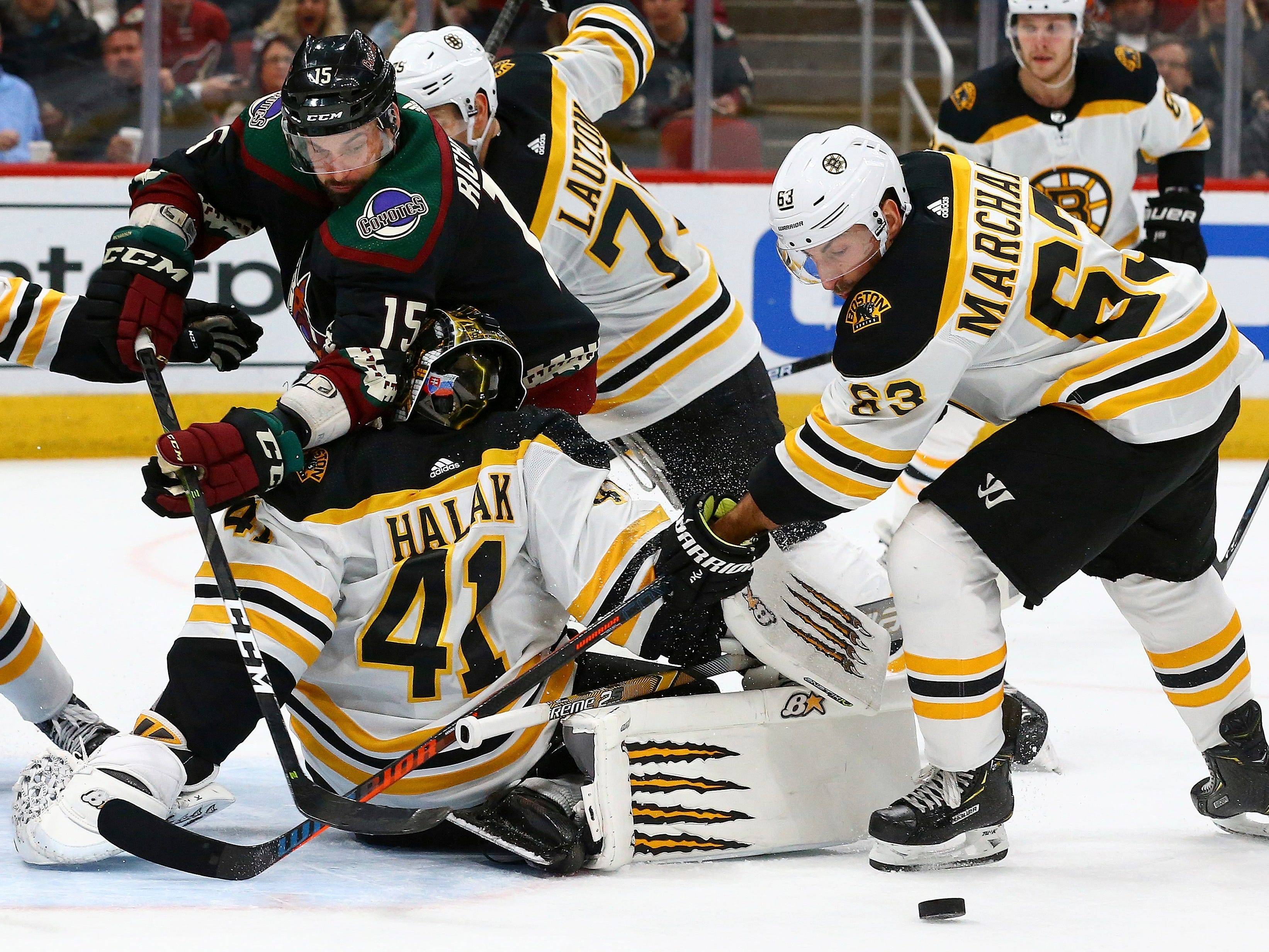 Arizona Coyotes center Brad Richardson (15) loses the puck as he collides with Boston Bruins goaltender Jaroslav Halak (41) while Bruins left wing Brad Marchand (63) watches the movement of the puck during the second period of an NHL hockey game Saturday, Nov. 17, 2018, in Glendale, Ariz. (AP Photo/Ross D. Franklin)