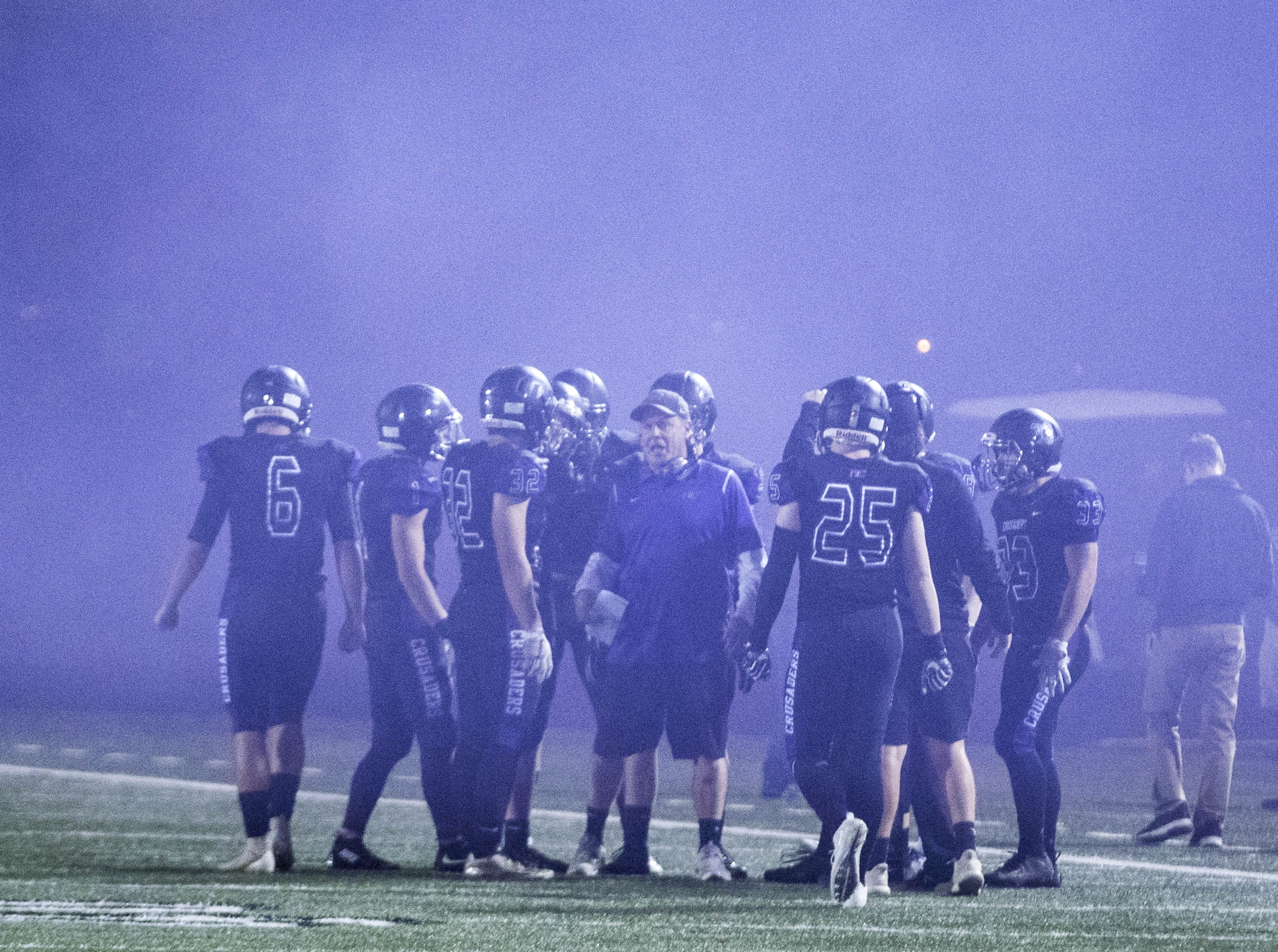 Under a cloud of smoke Northwest Christian coach David InnessÊrallies his players before their game with Valley Christian at North Canyon High School in Phoenix  Friday, Nov.17, 2018. #azhsfb