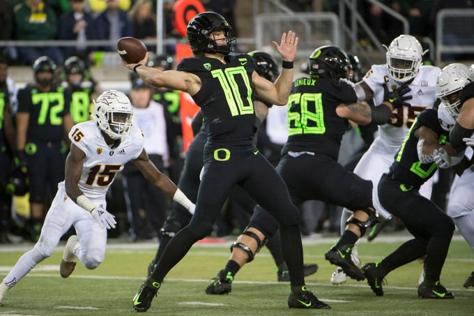 Nov 17, 2018; Eugene, OR, USA; Oregon Ducks quarterback Justin Herbert (10) throws a touchdown pass during the first half as he is pressured by Arizona State Sun Devils safety Cam Phillips (15) at Autzen Stadium. Mandatory Credit: Troy Wayrynen-USA TODAY Sports