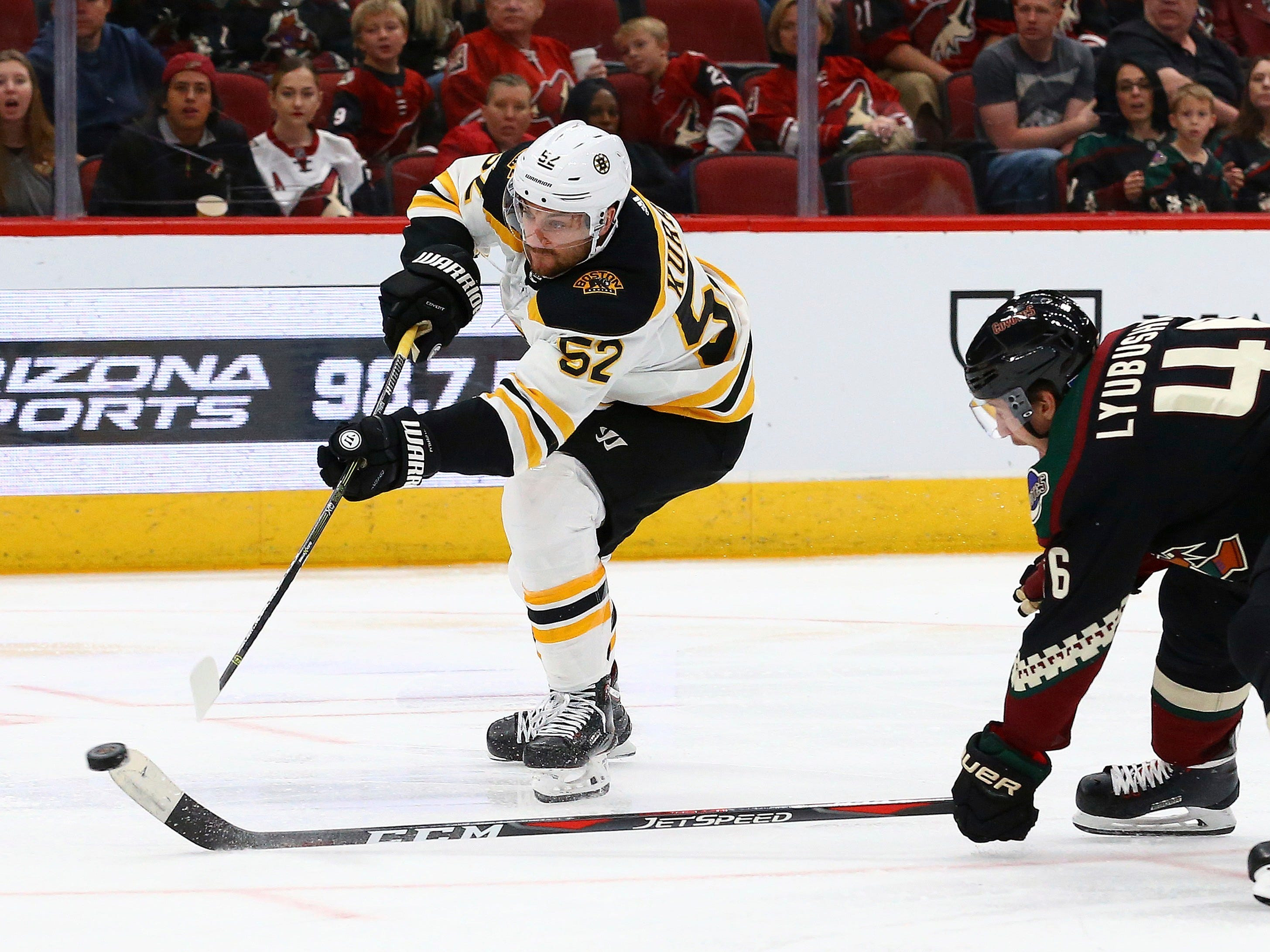 Boston Bruins center Sean Kuraly (52) shoots the puck past Arizona Coyotes defenseman Ilya Lyubushkin (46) during the third period of an NHL hockey game Saturday, Nov. 17, 2018, in Glendale, Ariz. The Bruins won 2-1. (AP Photo/Ross D. Franklin)