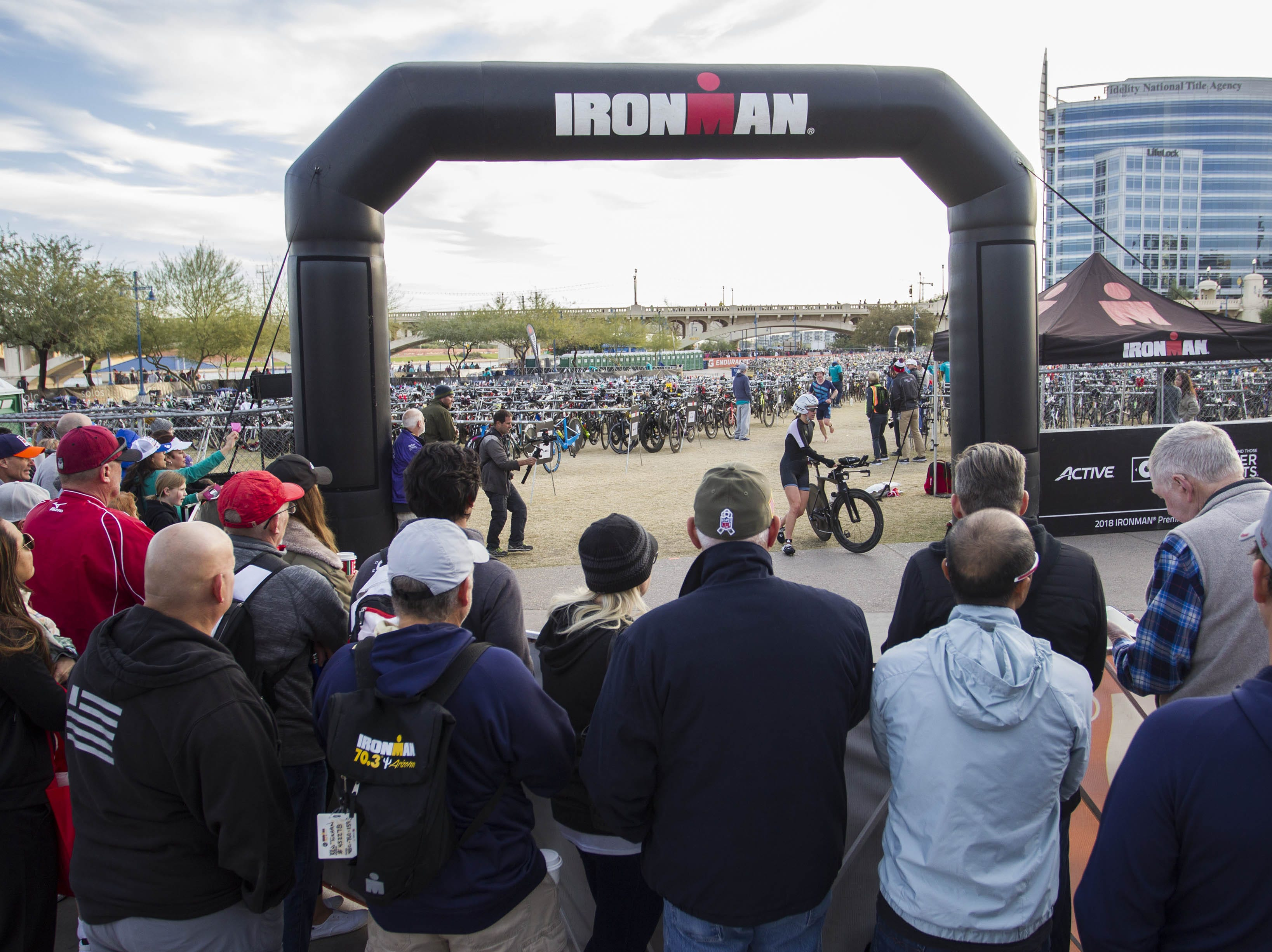 Fans of Ironman competitors watch as athletes start the bike portion of the race during the Tempe Ironman at Tempe Town Lake Nov.18, 2018.
