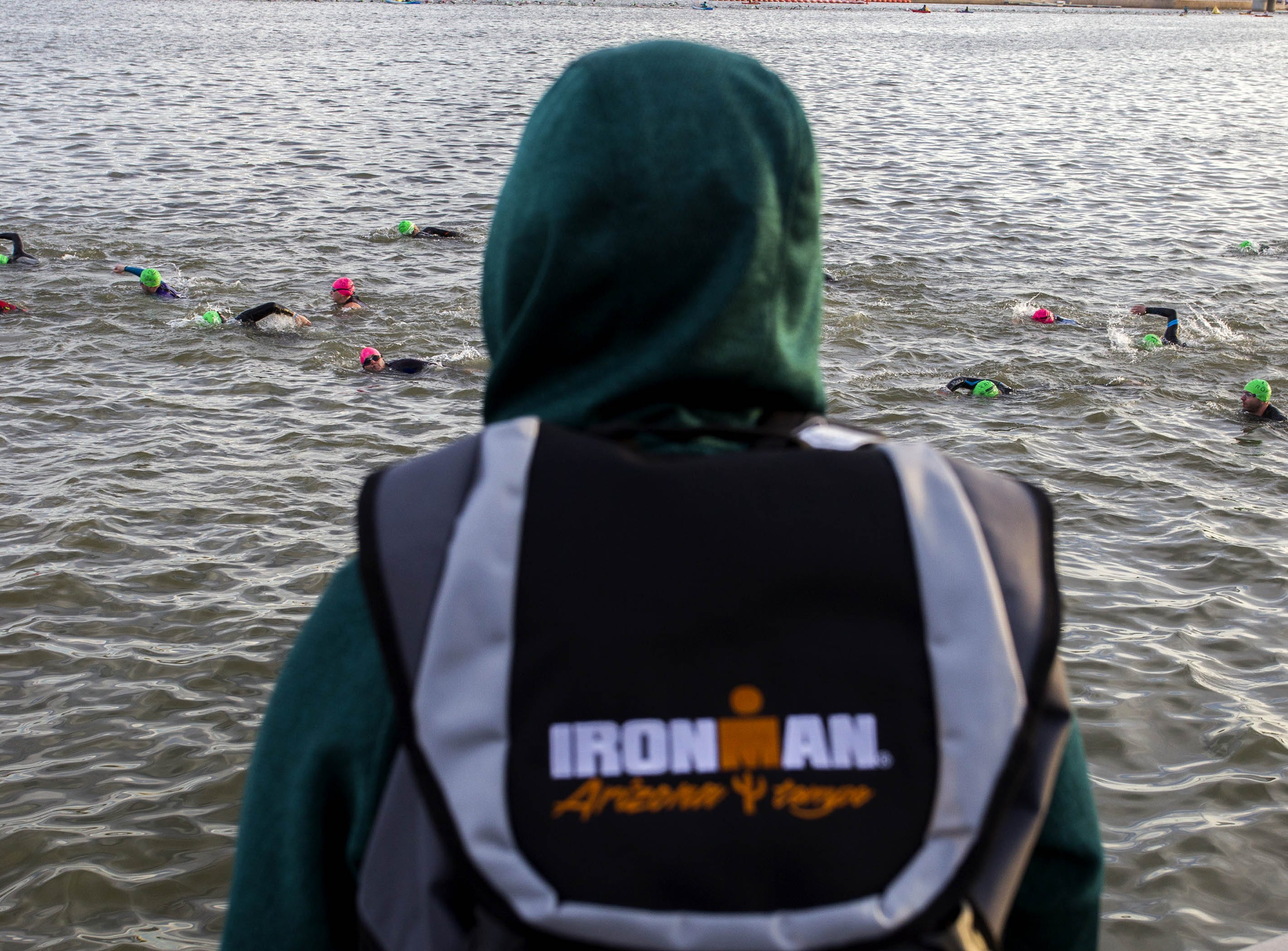 A fan of Ironman competitors watches as they start their day swimming during the Tempe Ironman at Tempe Town Lake Nov.18, 2018.