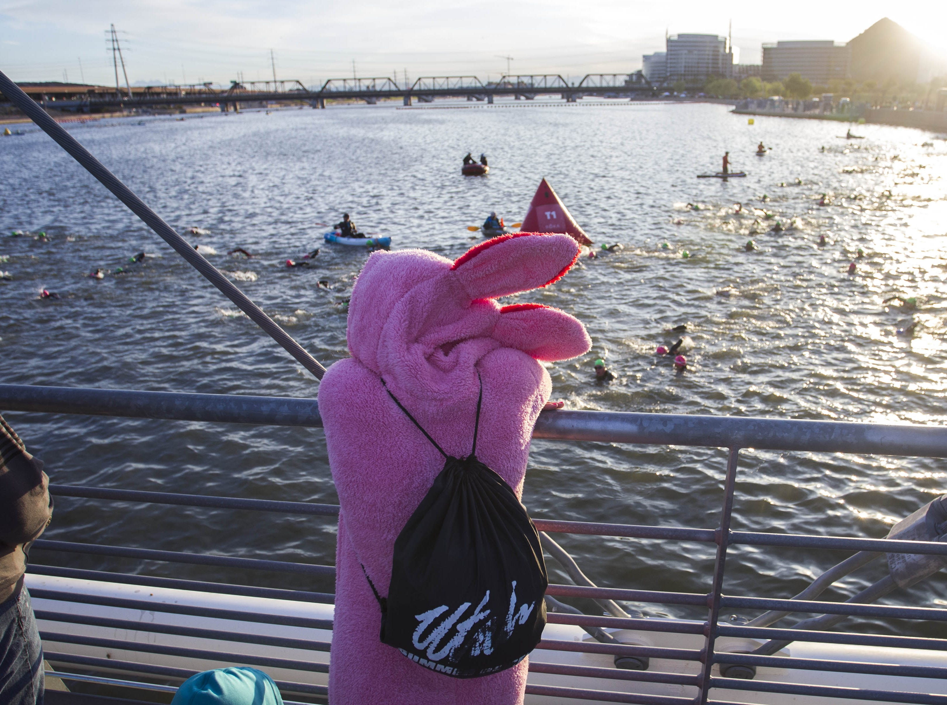 "A spectator wearing a ""bunny"" costume watches Ironman competitors start their day swimming during the Tempe Ironman at Tempe Town Lake Nov.18, 2018."