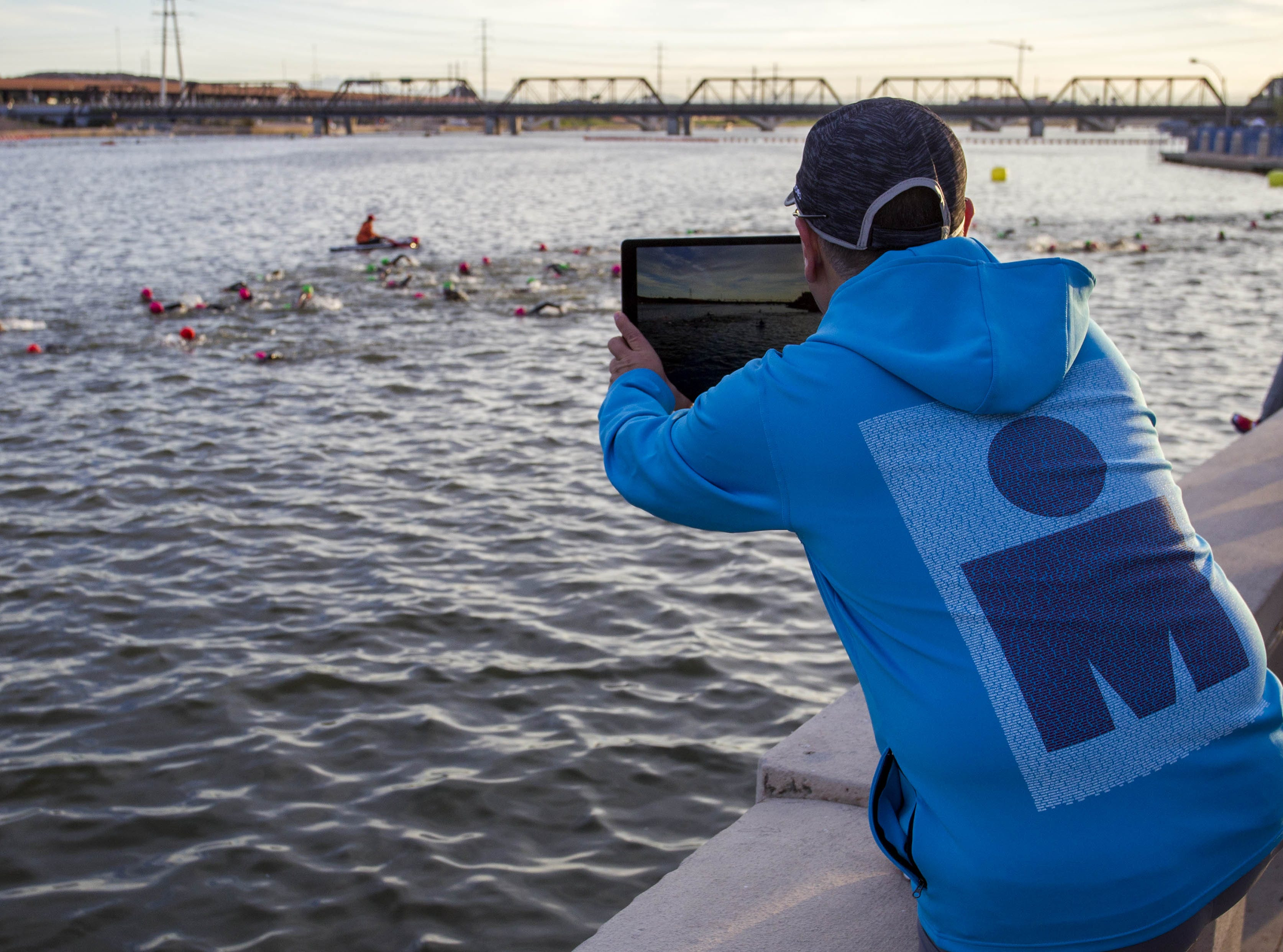A fan of Ironman competitors records them as they start their day swimming during the Tempe Ironman at Tempe Town Lake Nov.18, 2018.