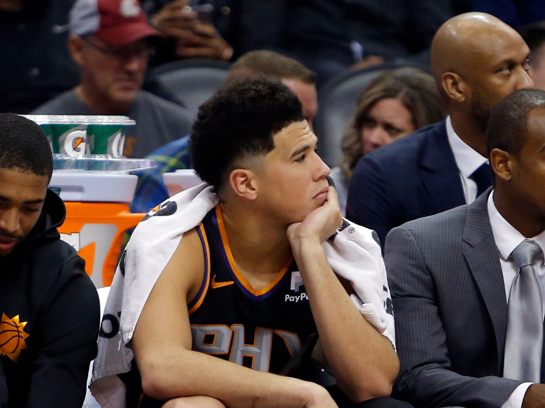 Phoenix Suns guard Devin Booker watches from the bench during the second half of the team's NBA basketball game against the Oklahoma City Thunder, Saturday, Nov. 17, 2018, in Phoenix. Oklahoma City won 110-100. (AP Photo/Rick Scuteri)