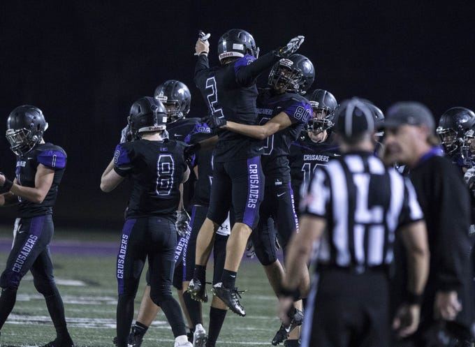 Northwest Christian's Adam Bunch (2) jumps into the arms of Chris Estrada (80) after their 27-6 win over Valley Christian at North Canyon High School in Phoenix  Friday, Nov.17, 2018. #azhsfb