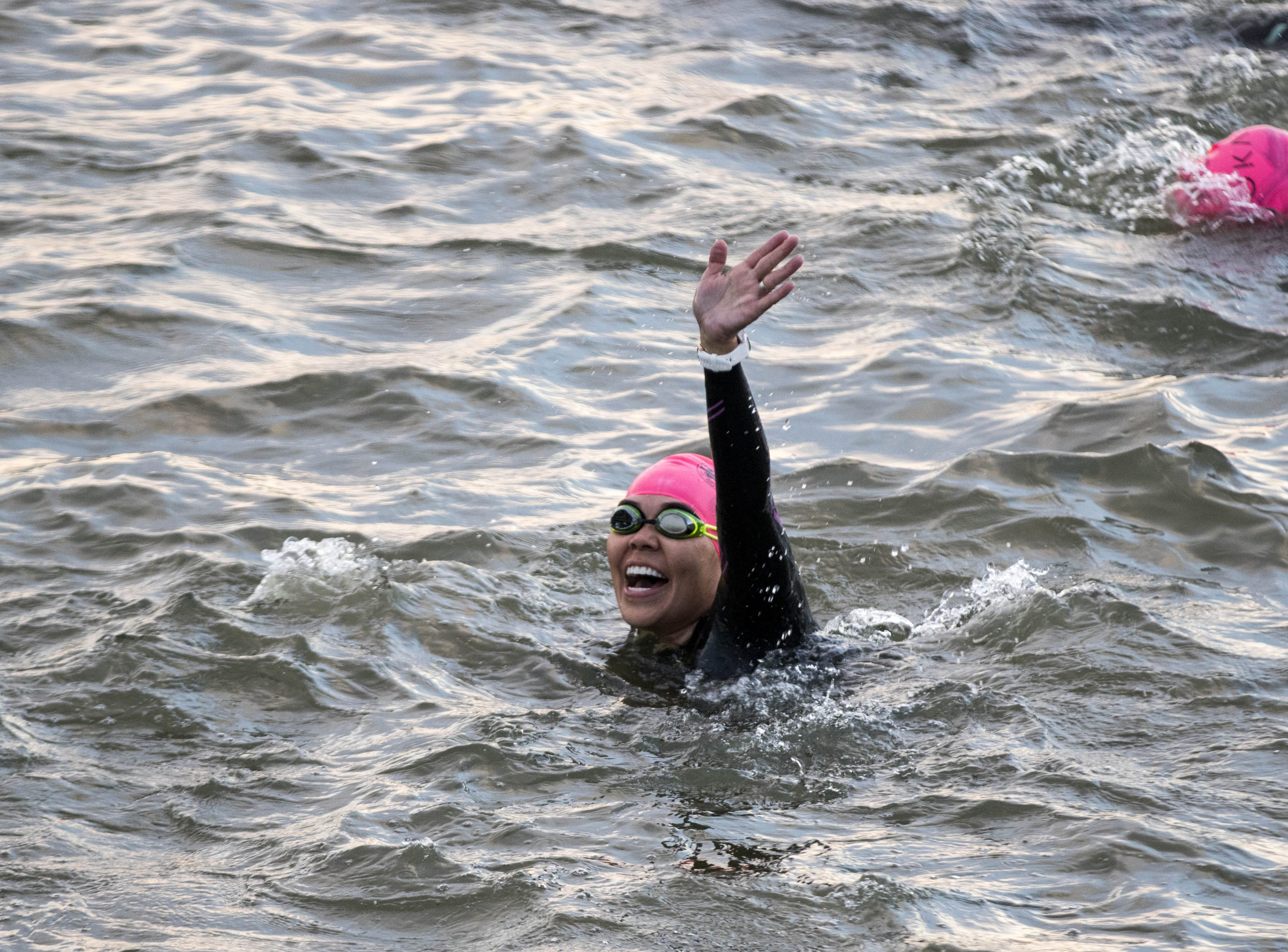 An Ironman competitor waves to their fans as she swims during the Tempe Ironman at Tempe Town Lake Nov.18, 2018.