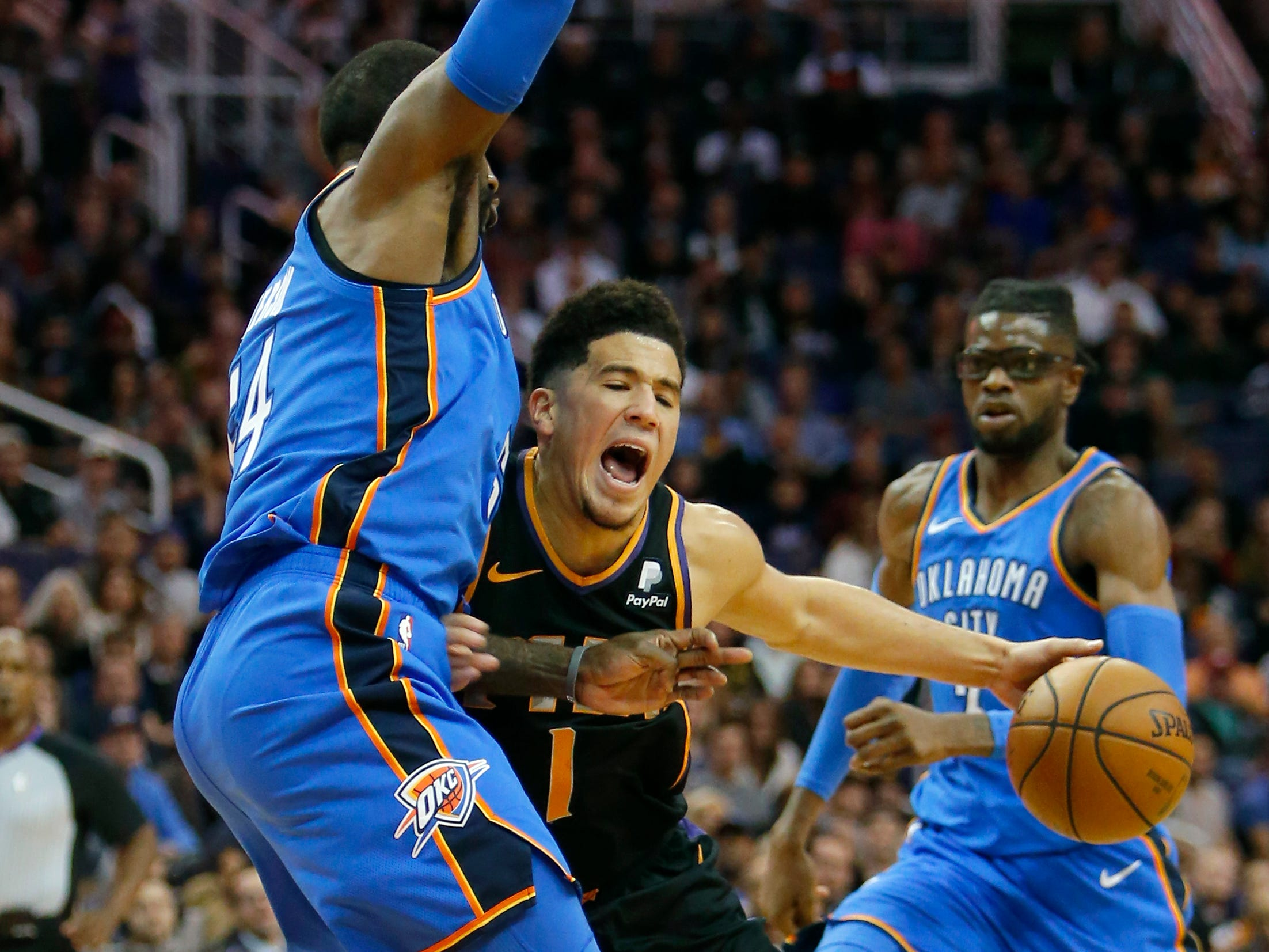 Phoenix Suns guard Devin Booker (1) drives on Oklahoma City Thunder forward Patrick Patterson during the first half of an NBA basketball game Saturday, Nov. 17, 2018, in Phoenix. (AP Photo/Rick Scuteri)