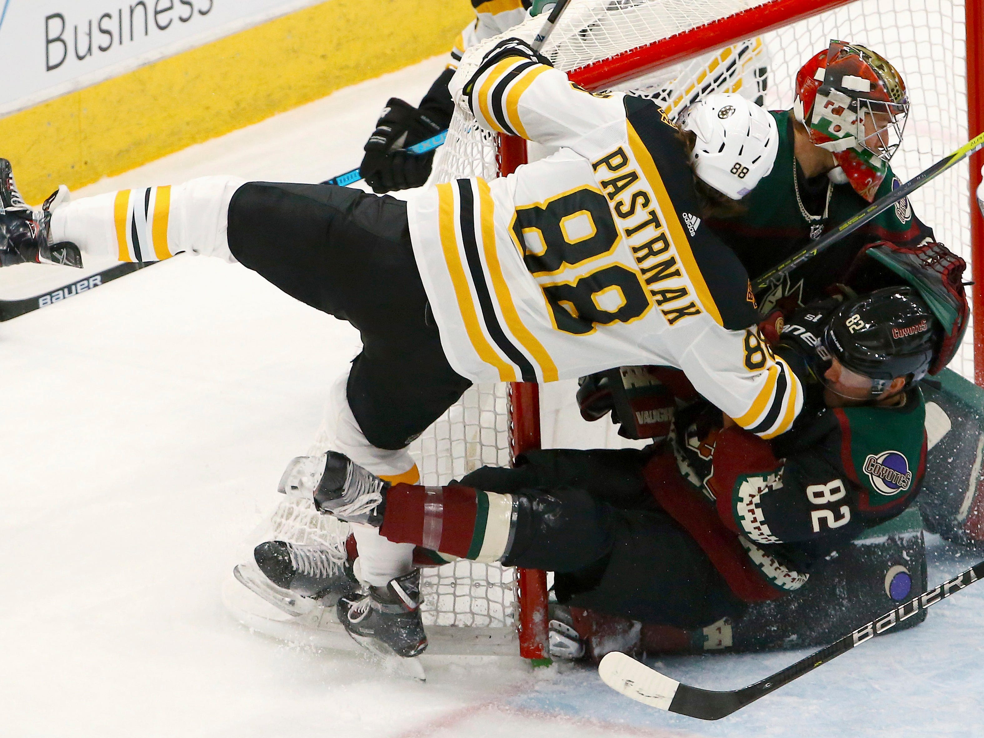 Boston Bruins right wing David Pastrnak (88) collides with Arizona Coyotes defenseman Jordan Oesterle (82) and Coyotes goaltender Darcy Kuemper, back right, during the first period of an NHL hockey game Saturday, Nov. 17, 2018, in Glendale, Ariz. (AP Photo/Ross D. Franklin)