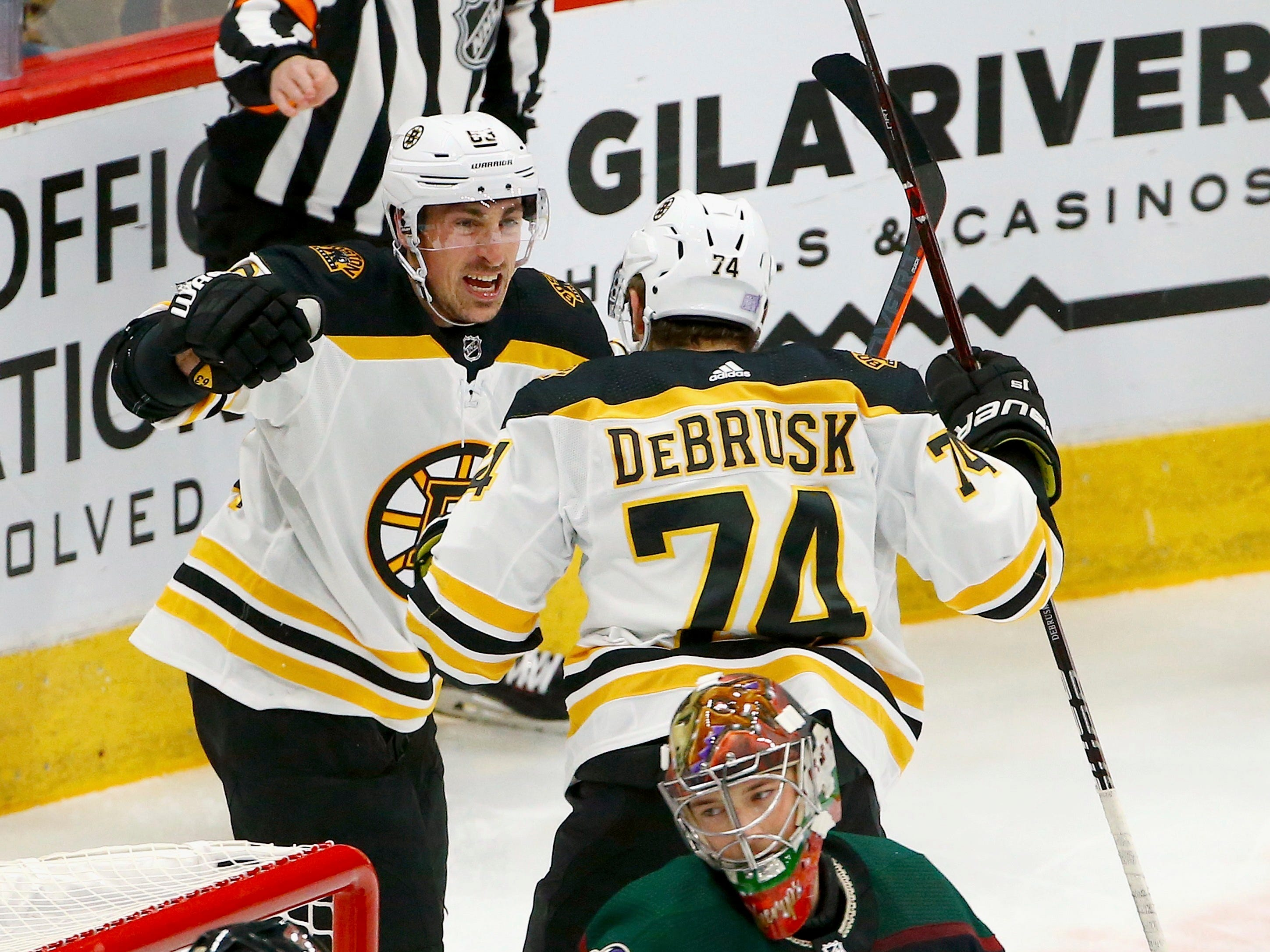 Boston Bruins left wing Jake DeBrusk (74) celebrates his goal against Arizona Coyotes goaltender Darcy Kuemper (35) with Bruins left wing Brad Marchand, top left, as Coyotes right wing Michael Grabner, left, pauses near the goal during the first period of an NHL hockey game Saturday, Nov. 17, 2018, in Glendale, Ariz. (AP Photo/Ross D. Franklin)