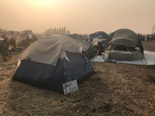 As seen on Nov. 17, a tent city developed in the field outside the Chico Walmart in California, where volunteers have collected donations and offered food and other services since the fire. The camp is set to close Nov. 18 to transition people to traditional shelters; however, people don't want re-locate again after finding a sense of community.