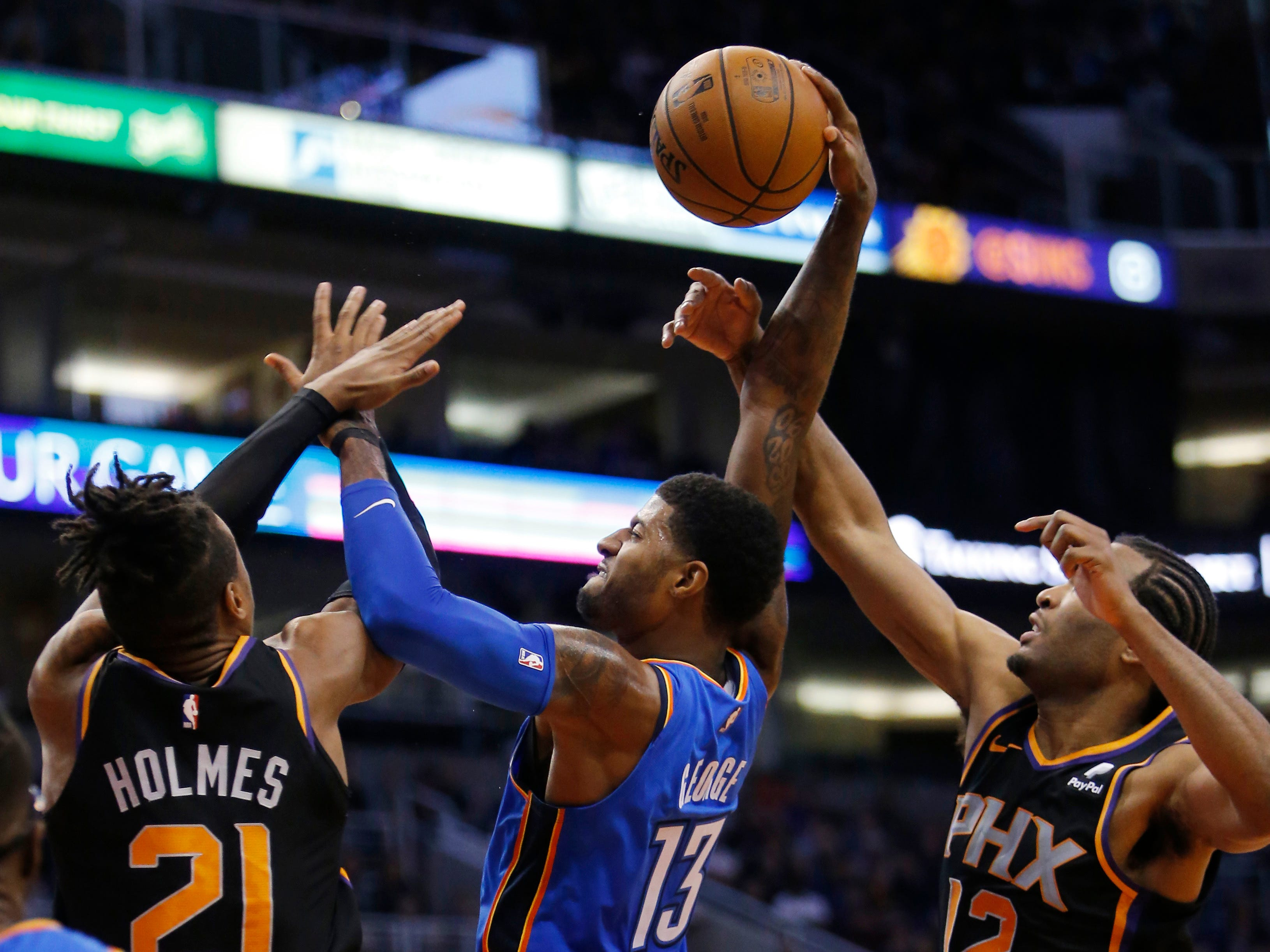 Oklahoma City Thunder forward Paul George (13) drives between Phoenix Suns forward Richaun Holmes and TJ Warren (12) during the second half of an NBA basketball game Saturday, Nov. 17, 2018, in Phoenix. Oklahoma City won 110-100. (AP Photo/Rick Scuteri)