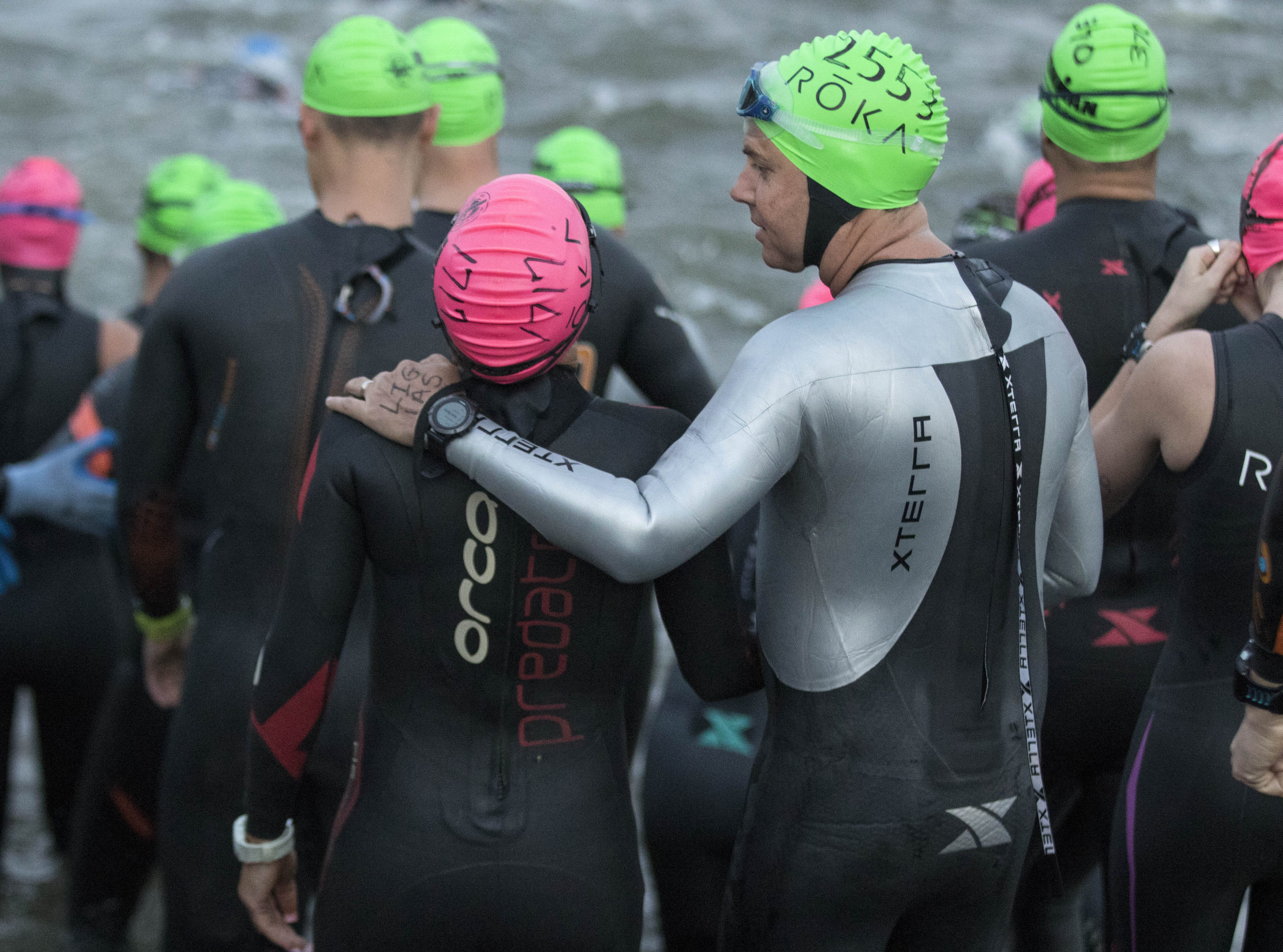 An Ironman competitor gets last-minute encouragement as they start their swim during the Tempe Ironman at Tempe Town Lake Nov.18, 2018.