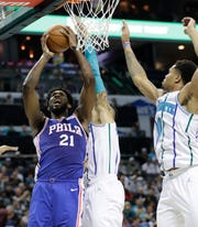 Philadelphia 76ers' Joel Embiid (21) shoots against Charlotte Hornets' Willy Hernangomez (41) and Miles Bridges (0) during the second half of an NBA basketball game in Charlotte, N.C., Saturday, Nov. 17, 2018. (AP Photo/Chuck Burton)