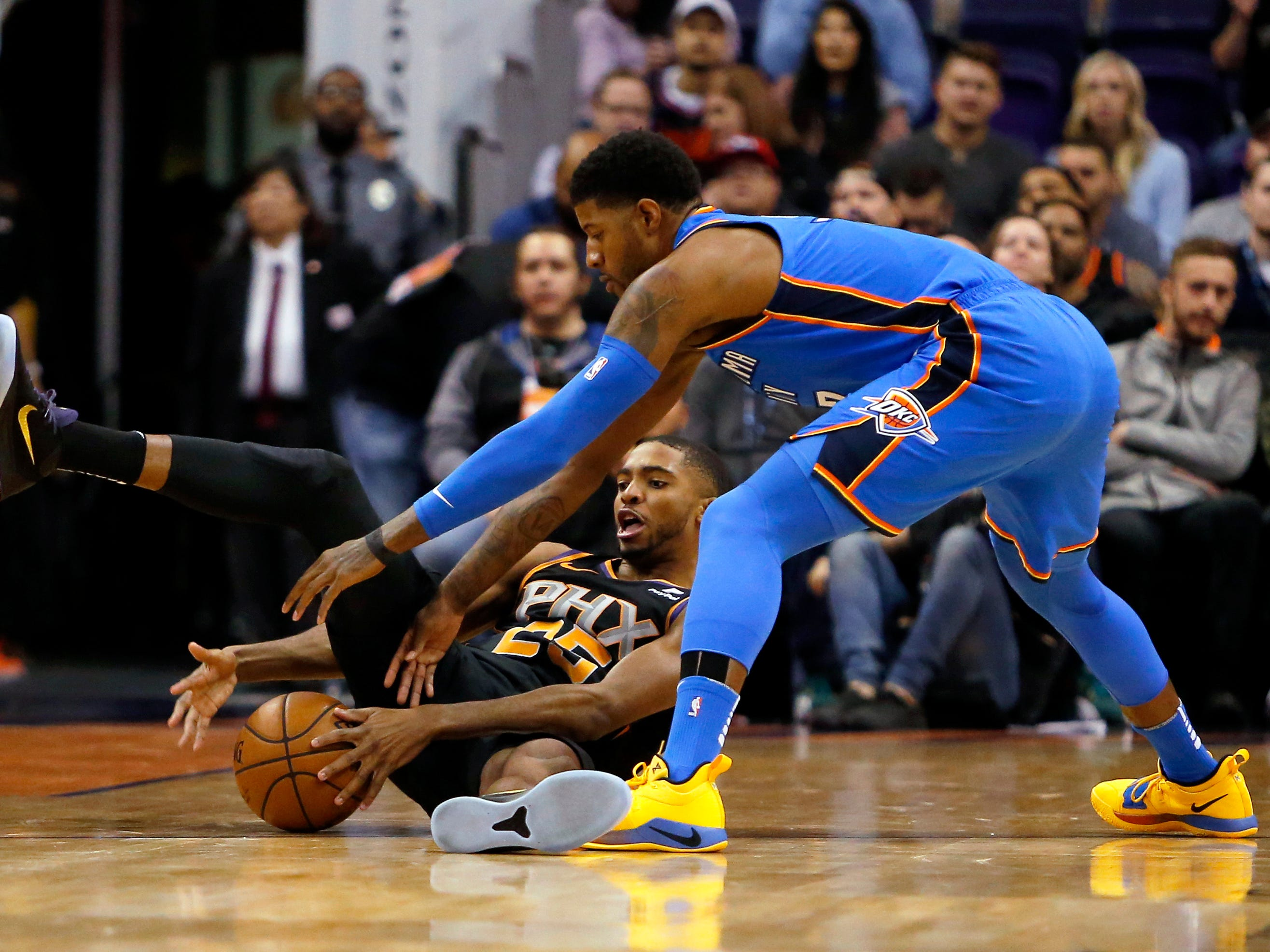 Phoenix Suns forward Mikal Bridges (25) and Oklahoma City Thunder forward Paul George reach for a loose ball during the first half of an NBA basketball game Saturday, Nov. 17, 2018, in Phoenix. (AP Photo/Rick Scuteri)