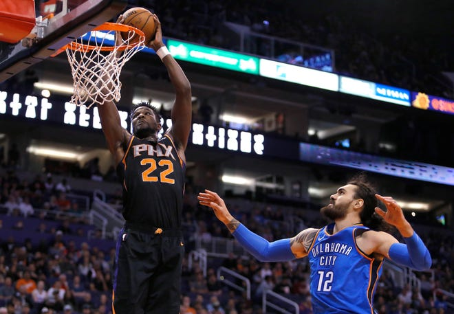 Phoenix Suns center Deandre Ayton (22) drives past Oklahoma City Thunder center Steven Adams during the first half during an NBA basketball game Saturday, Nov. 17, 2018, in Phoenix. (AP Photo/Rick Scuteri)