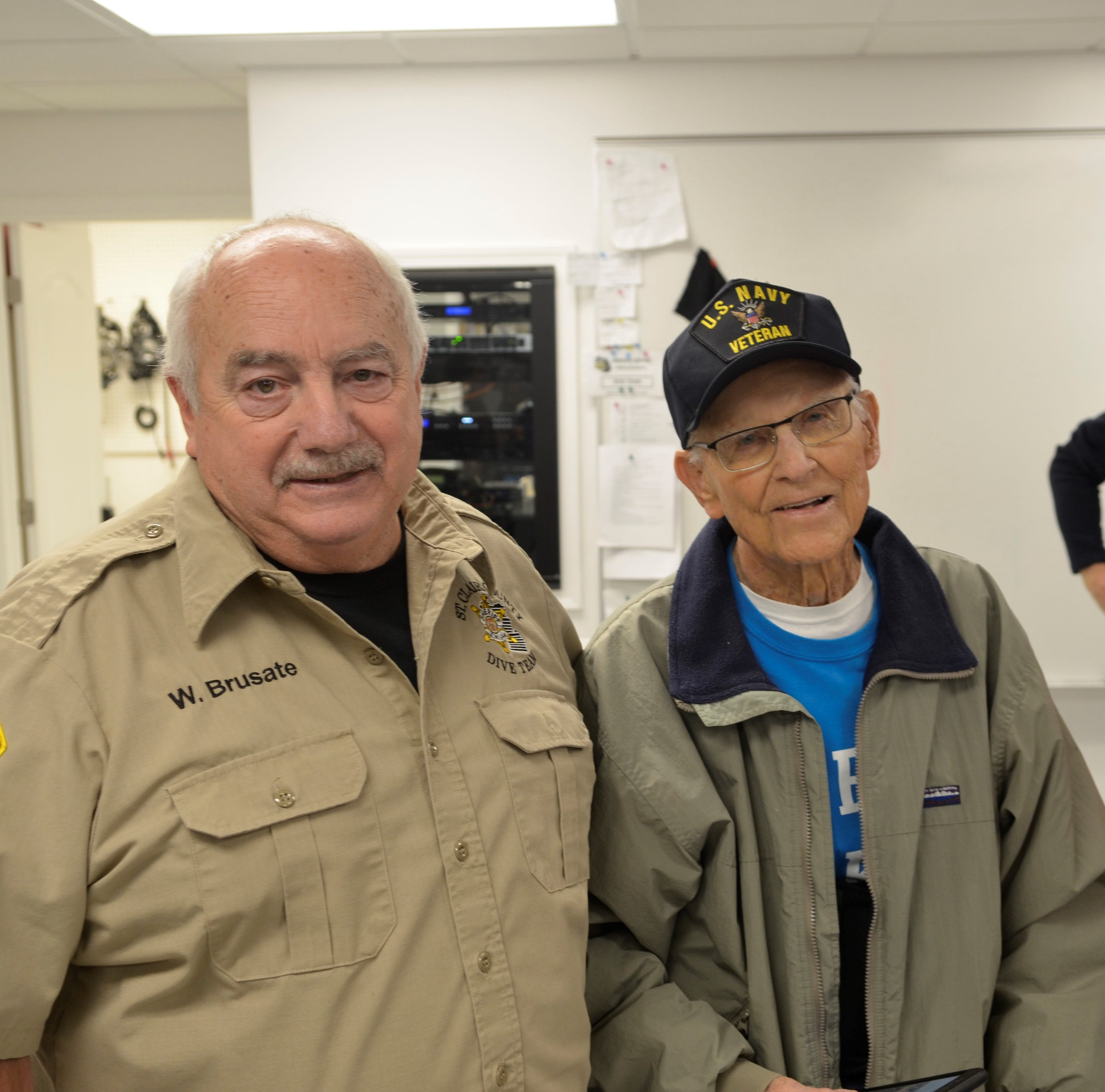 From left, Wayne Brusate and Don Evans stand together at an open house for the St. Clair County Dive Team on Nov. 18, 2018, in Marysville, Michigan. . The team is working to learn more about its early years and to recruit new members.