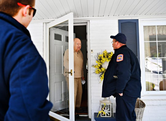 Fire Chief Nate Tracey, right, and volunteer firefighter Brandon Poole, left, of York Township Fire Department, are greeted at the door by resident Howard Yoder, 83, as they canvas homes in York Township, offering safety checks and replacements to ensure that residents have functioning smoke detectors in their homes, Saturday, Nov. 17, 2018. Tracey and his crew would replace three detectors in Yoder's home. Dawn J. Sagert photo