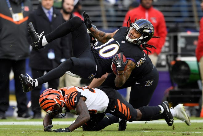 Baltimore Ravens wide receiver Chris Moore (10) flips over Cincinnati Bengals cornerback Tony McRae as he rushes the ball in the second half of an NFL football game, Sunday, Nov. 18, 2018, in Baltimore. (AP Photo/Nick Wass)