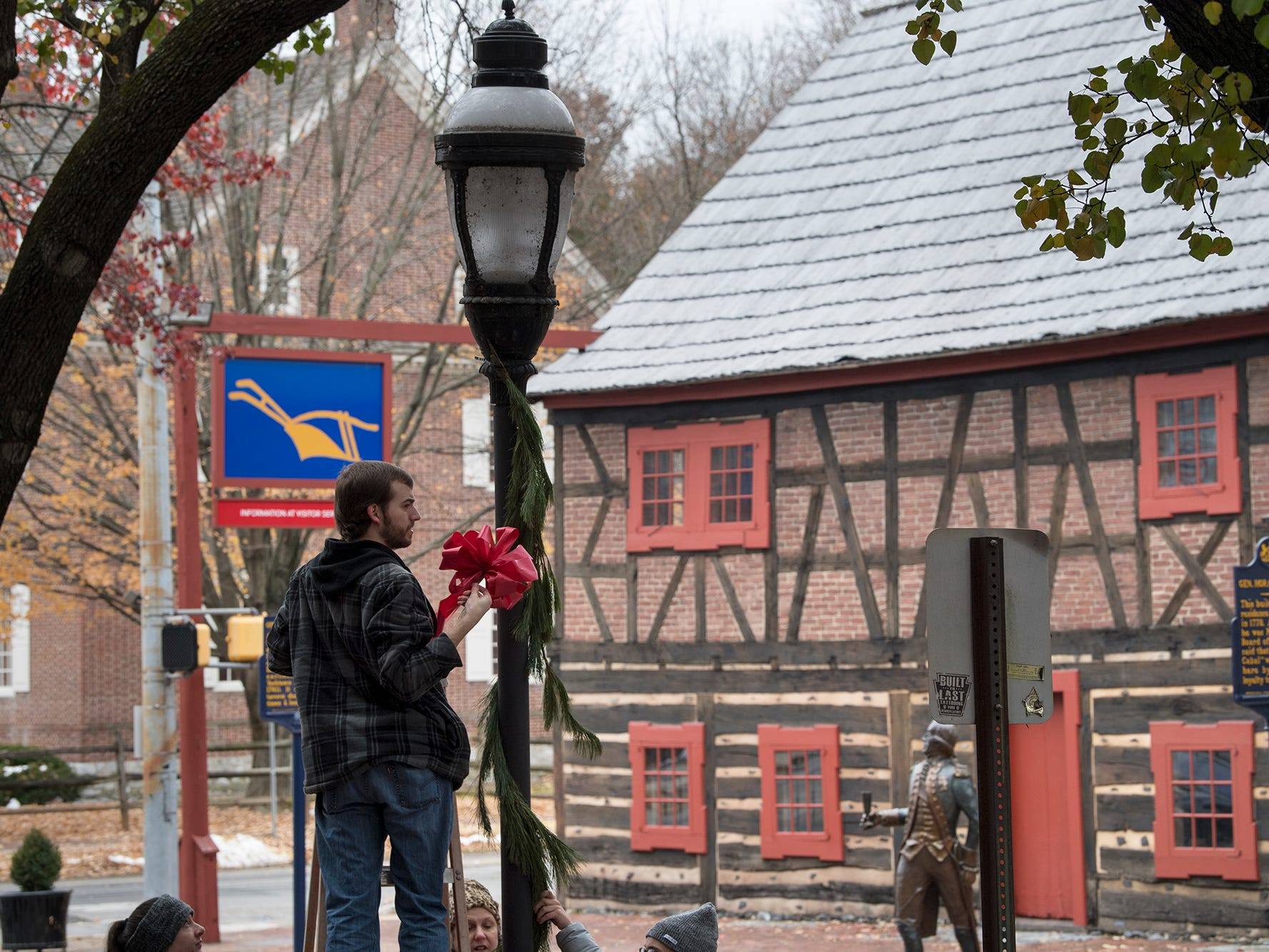 Zach Galloway, a volunteer with RLK, ties a bow on a lamppost near the Golden Plough Tavern and Gates House during the Hanging of the Greens around Continental Square in York on Sunday.
