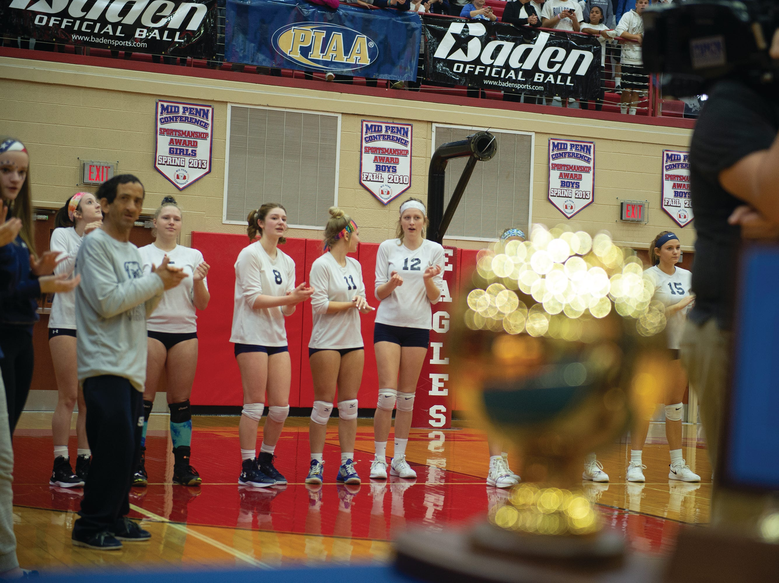 The West York girls' volleyball team waits to receive their gold medals and the PIAA Class 3A championship trophy (foreground).
