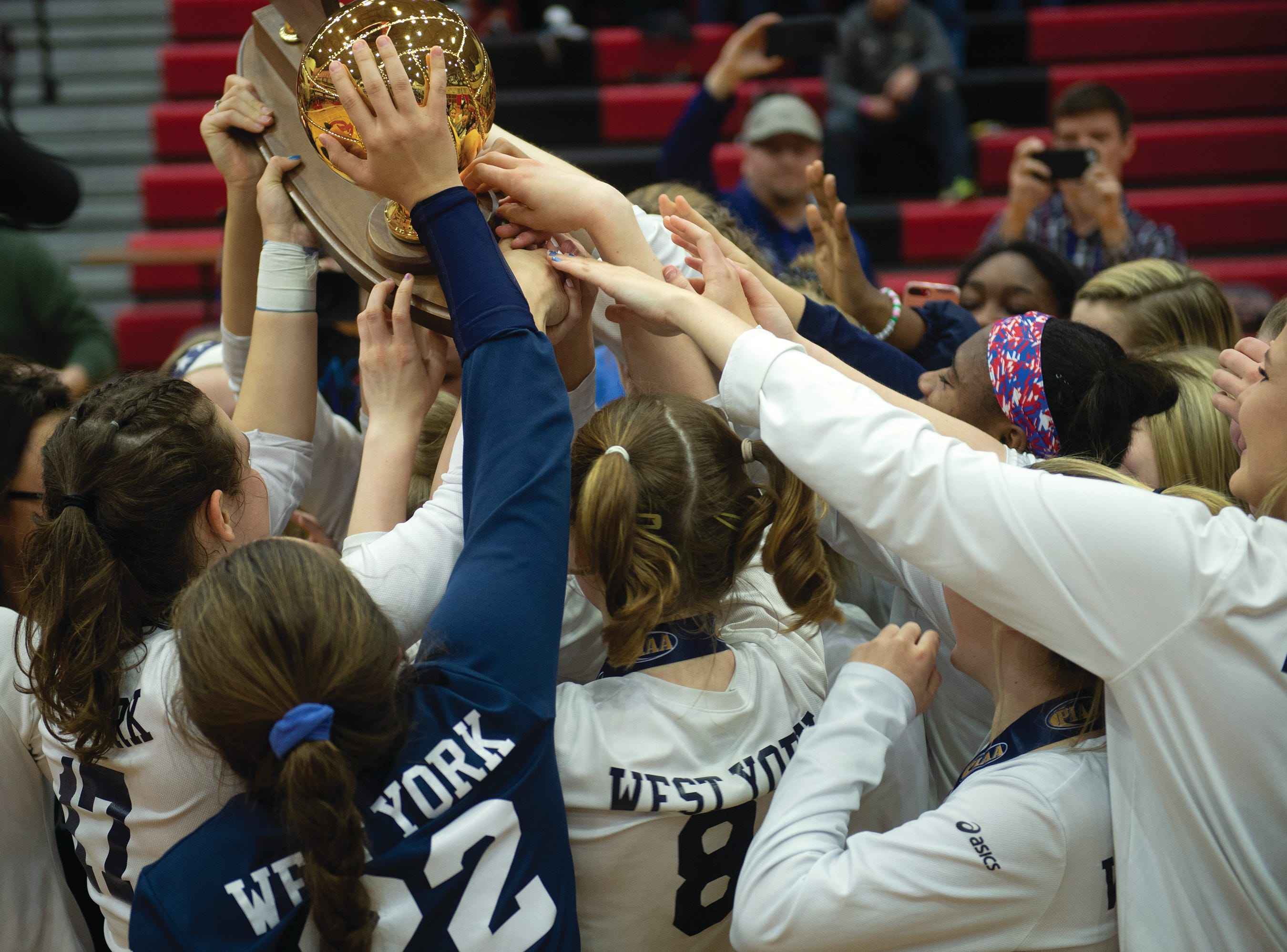 West York players reach for the PIAA Class 3A girls' volleyball trophy after the Bulldogs defeated Warren 3-0 Saturday at Cumberland Valley High School.