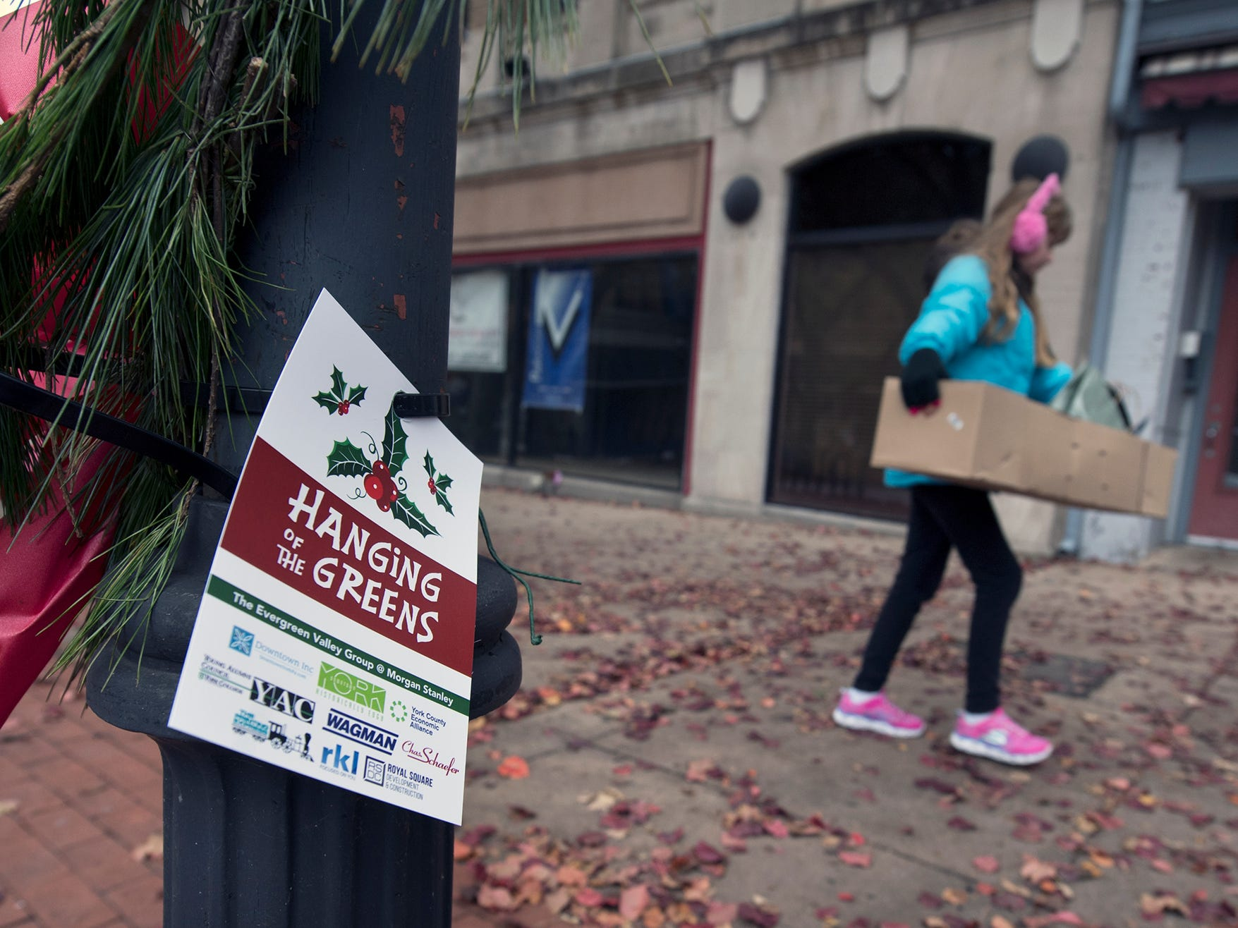 Kaylanna White, 11, carries a box of greens to the next light post during the Hanging of the Greens around Continental Square in York Sunday November 18, 2018.