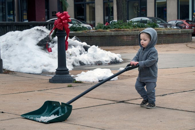 Jacob Chesla, 2, helps clean up after Hanging of the Greens around Continental Square in York on Sunday.