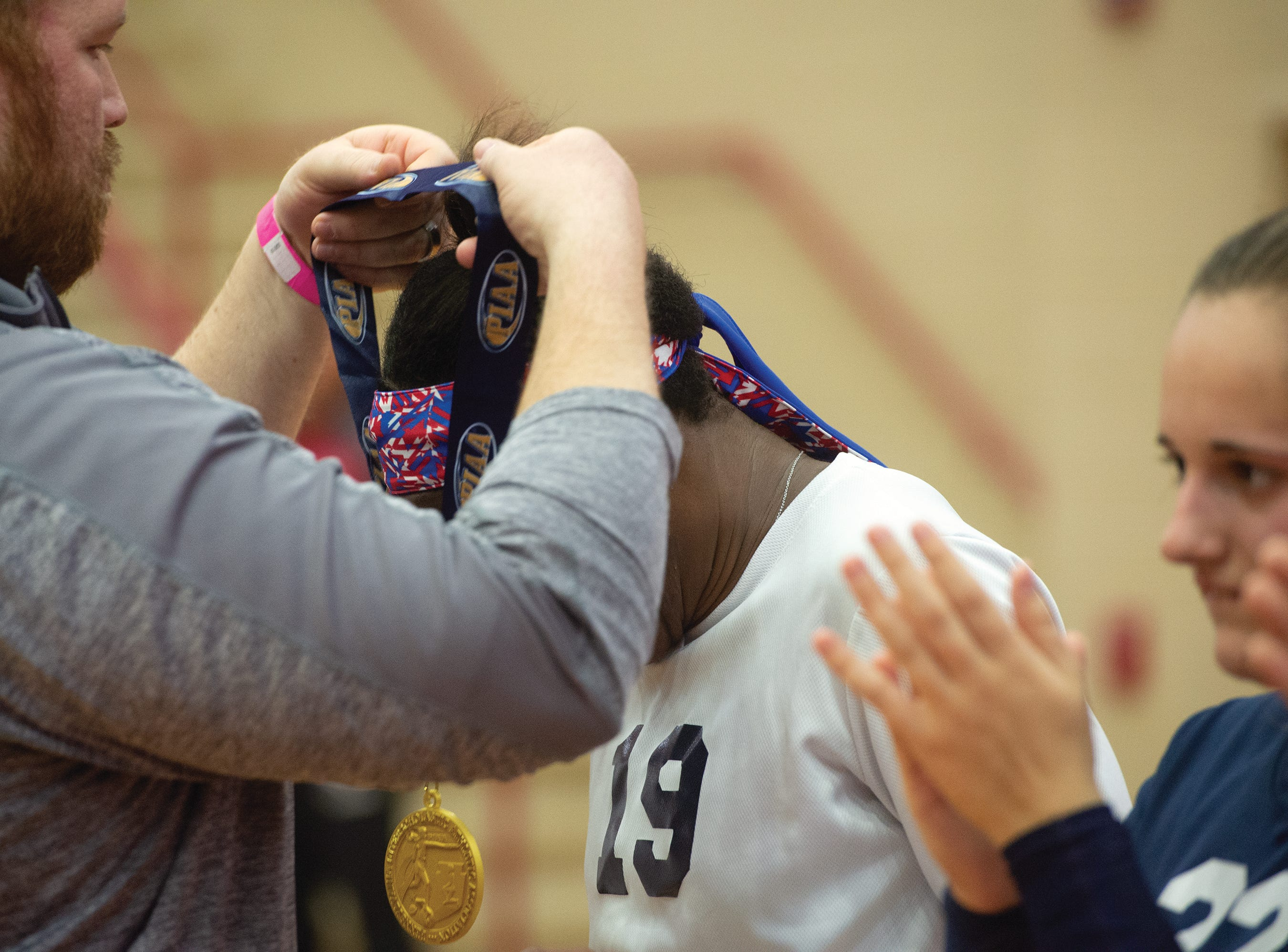 West York coach puts a gold medal around the neck of middle hitter Tesia Thomas. The Bulldogs defeated Warren 3-0 Saturday to win the PIAA Class 3A girls' volleyball title.