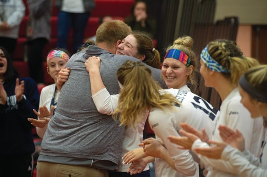 Julia Rill hugs West York coach Joe Ramp after he presented her with a gold medal Saturday. The Bulldogs defeated Warren 3-0 to claim the PIAA Class 3A girls' volleyball title.