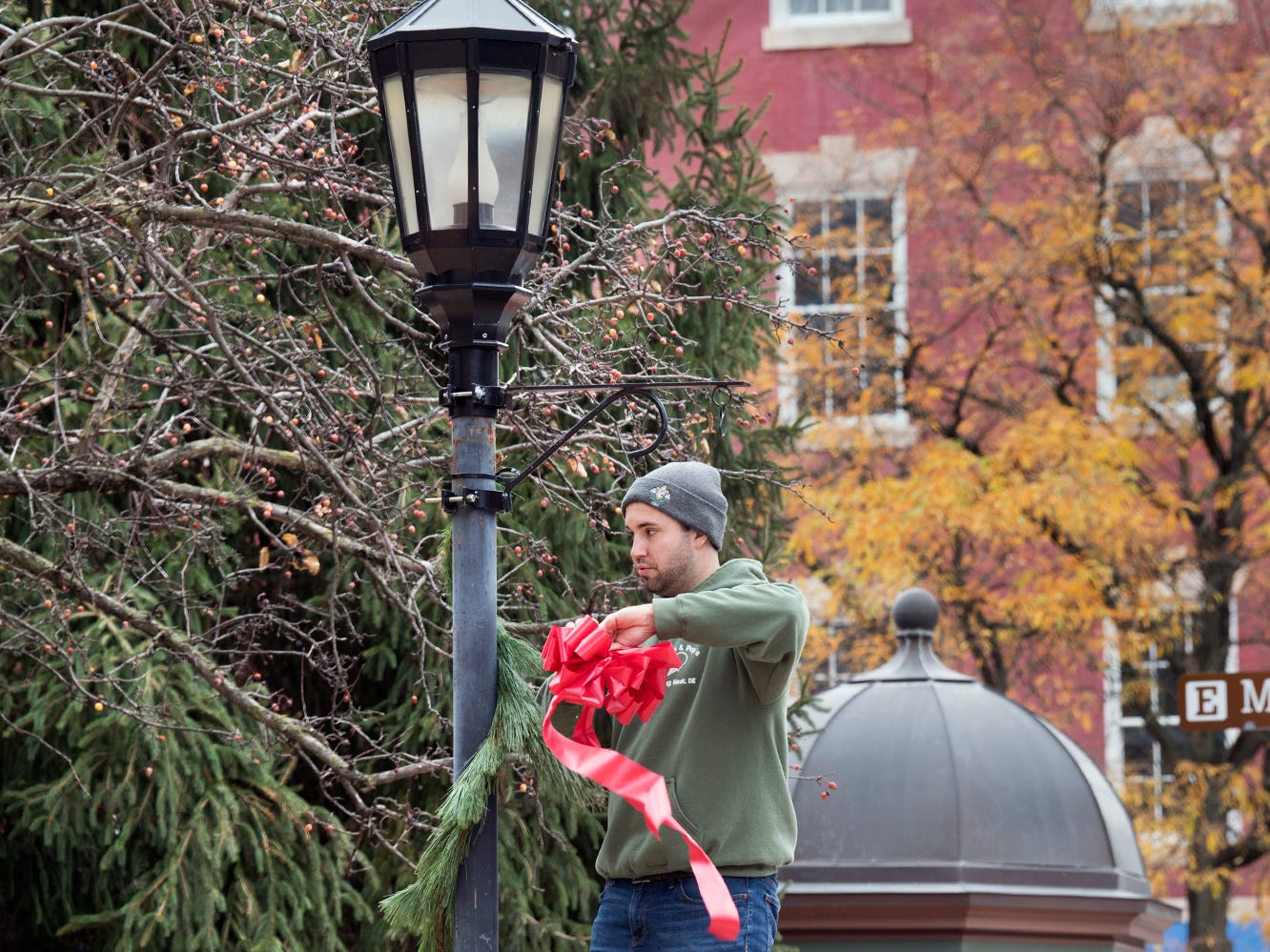 From the left, Julie Kaizar, Tom Kaizar and Kevin Wilcox, volunteers from RKL, decorate a light post on Continental Square during the Hanging of the Greens around Continental Square in York on Sunday. The decorations help put people in the holiday spirit, and also prepare for Light Up York on Dec. 1.