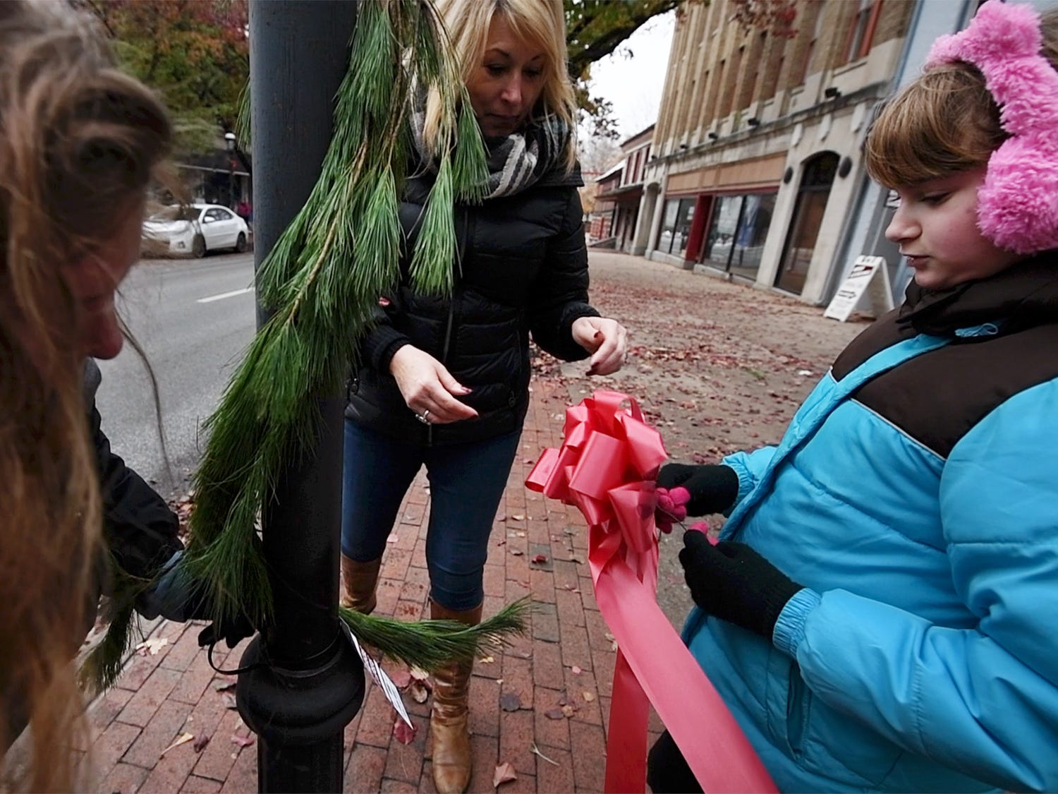 From the left, Michelle Frye, Lori Evans, and Kaylanna White, 11, tie a bow to the the bottom greenery on West Market Street during the Hanging of the Greens Sunday November 18, 2018.