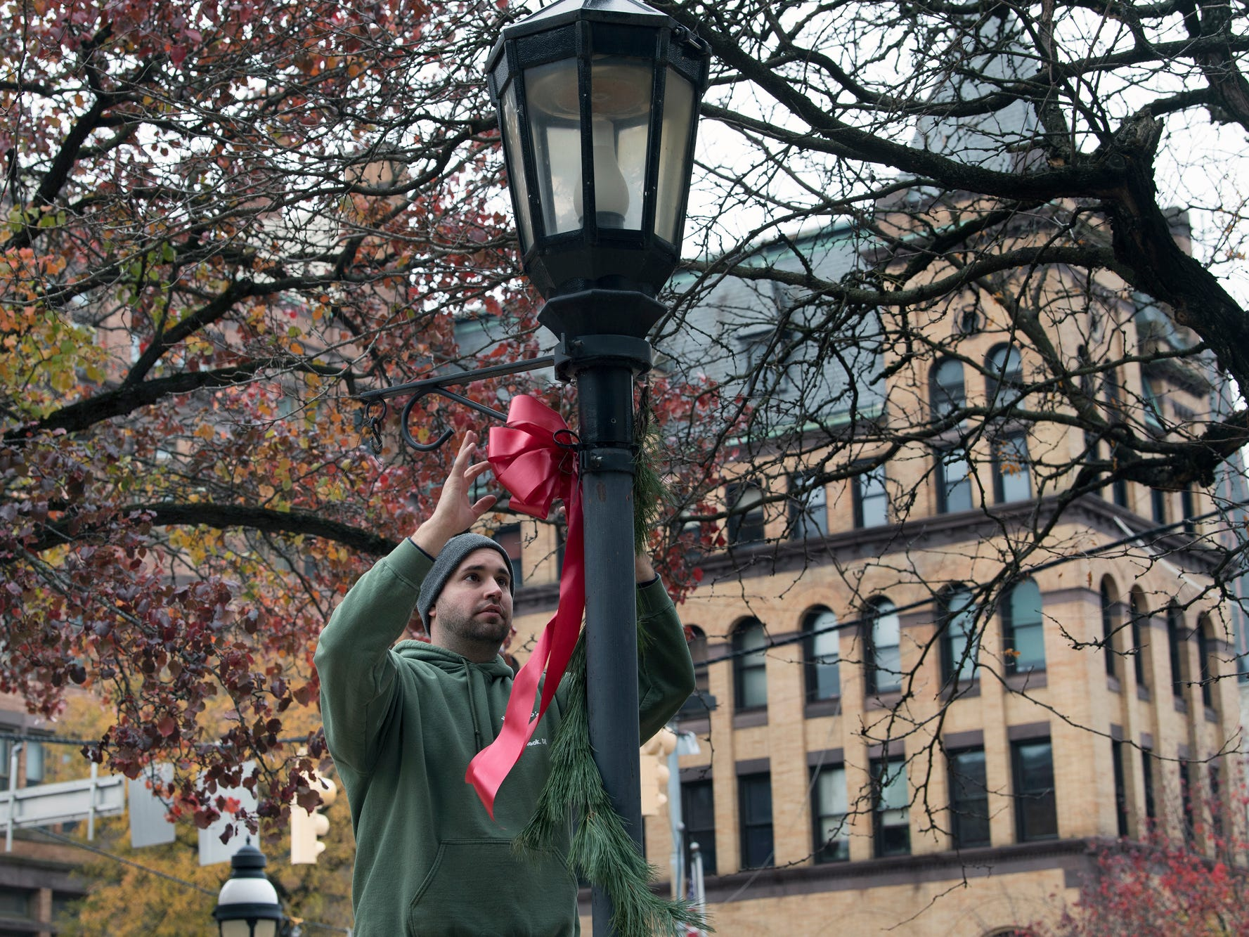 Tom Kaizar decorates a lamppost during the Hanging of the Greens around Continental Square in York Sunday November 18, 2018.