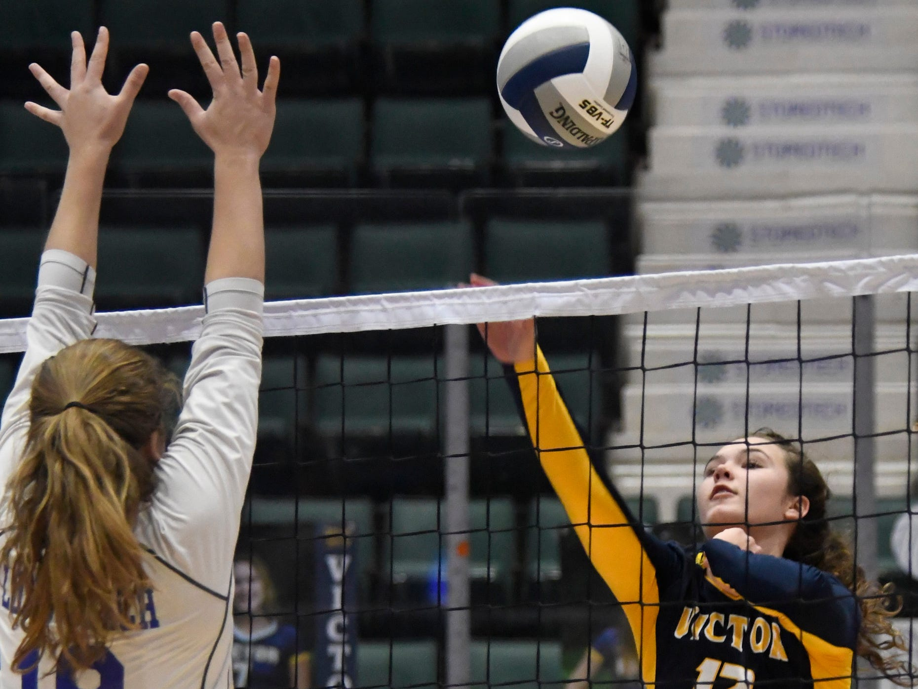 Victor's Emma Werkmeister hits the ball past a block by Long Beach's Marlene Kramer during the Class AA state final on Sunday.