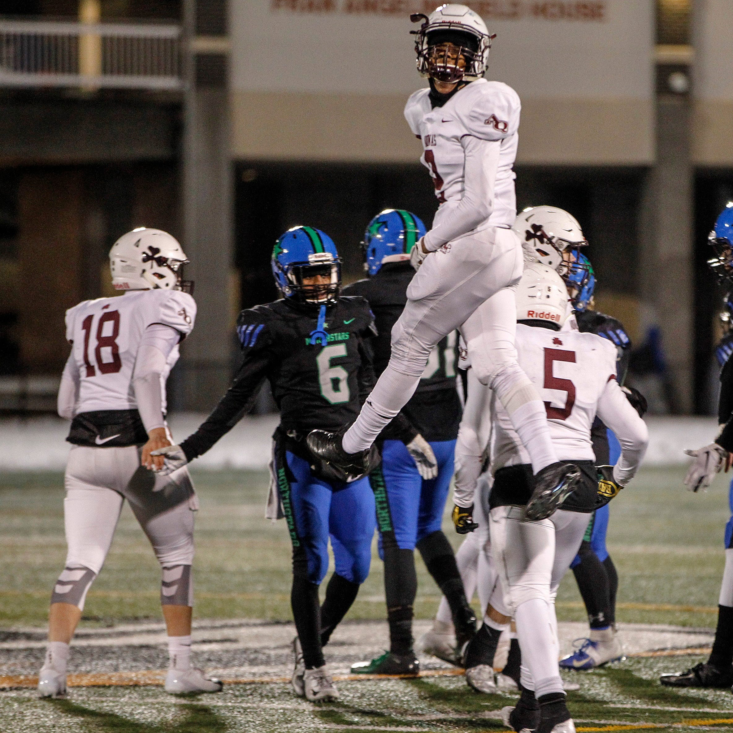 Aquinas' Kobe McNair jumps as he celebrates victory over Cicero-North at Union-Endicott High School during state semifinals. Saturday, November 17, 2018.