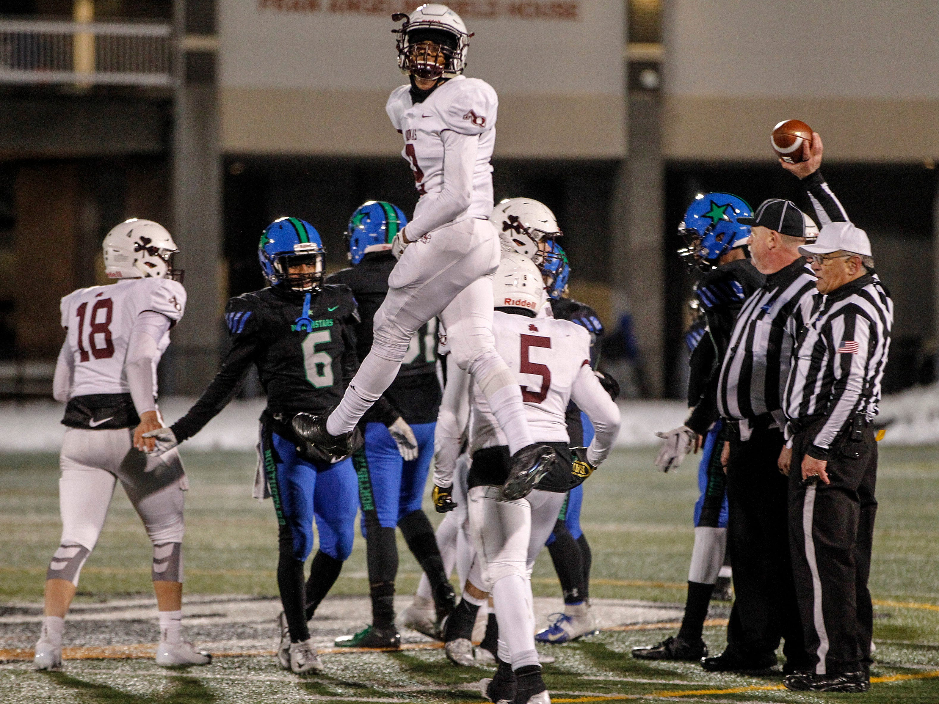 Aquinas' Kobe McNair jumps as he celebrates victory over Cicero-North at Union-Endicott High School during state semifinals. Saturday, November 17, 2018.