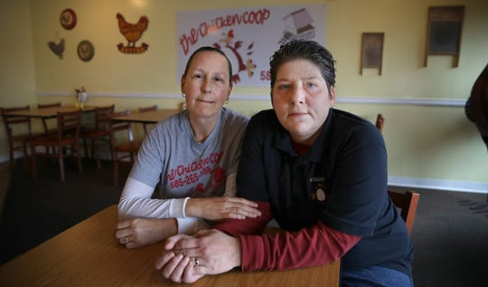 Brandie Rauber-Wasson, right, and her wife, Christina Rauber-Wasson, sit together inside their BC's Chicken Coop restaurant in Webster Sunday, Nov. 18, 2018. They empathize with what Emily Scheck is going through.