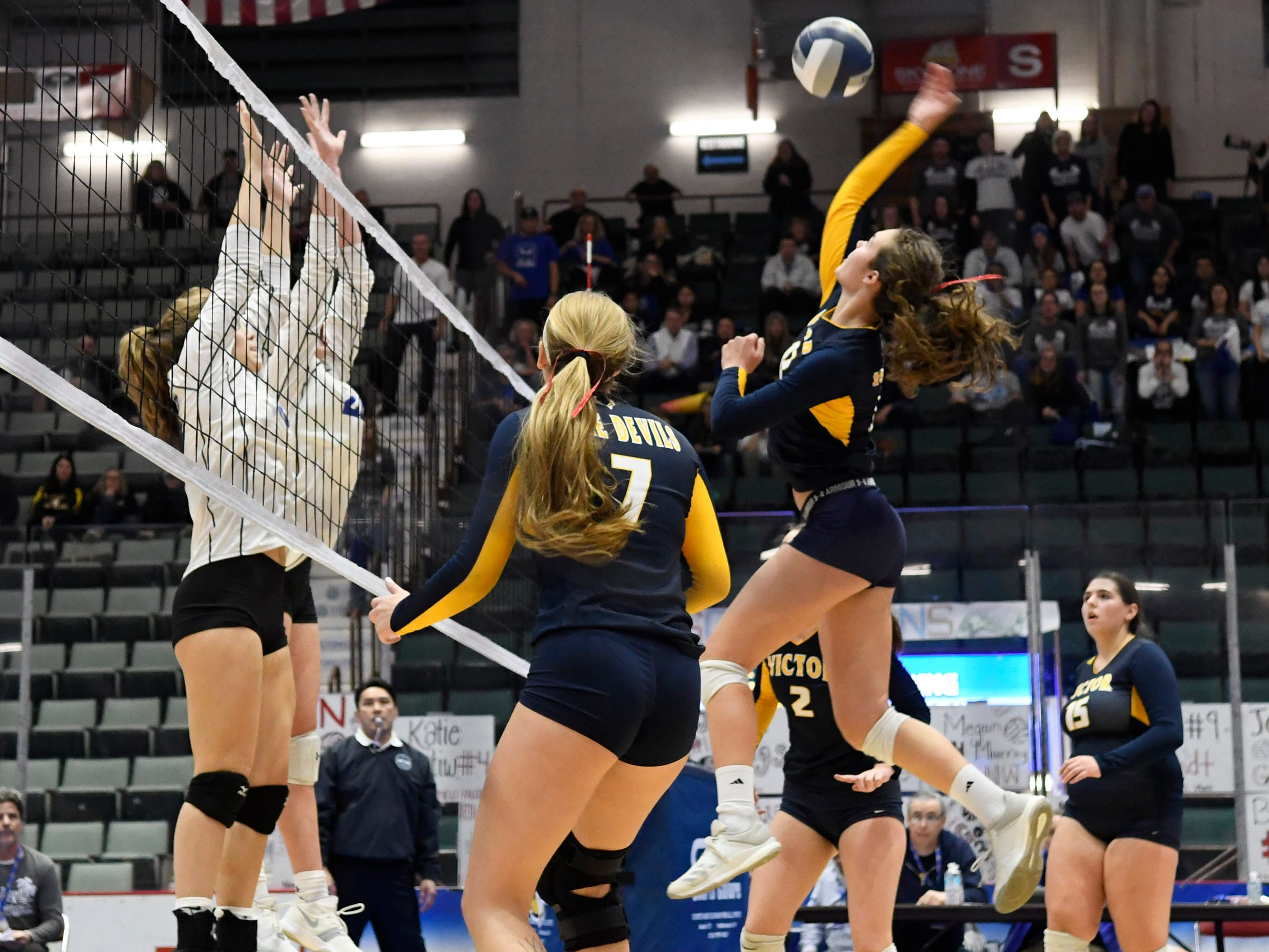 Victor's Emma Werkmeister spikes the ball as Long Beach players jump to block it during the Class AA state final on Sunday in Glens Falls.