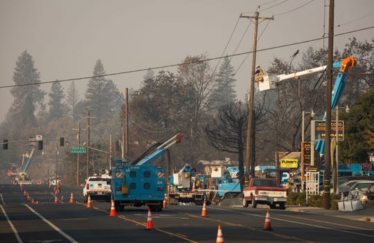 PG&E trucks work in the devastated town of Paradise last fall to restore power infrastructure following the Camp Fire.