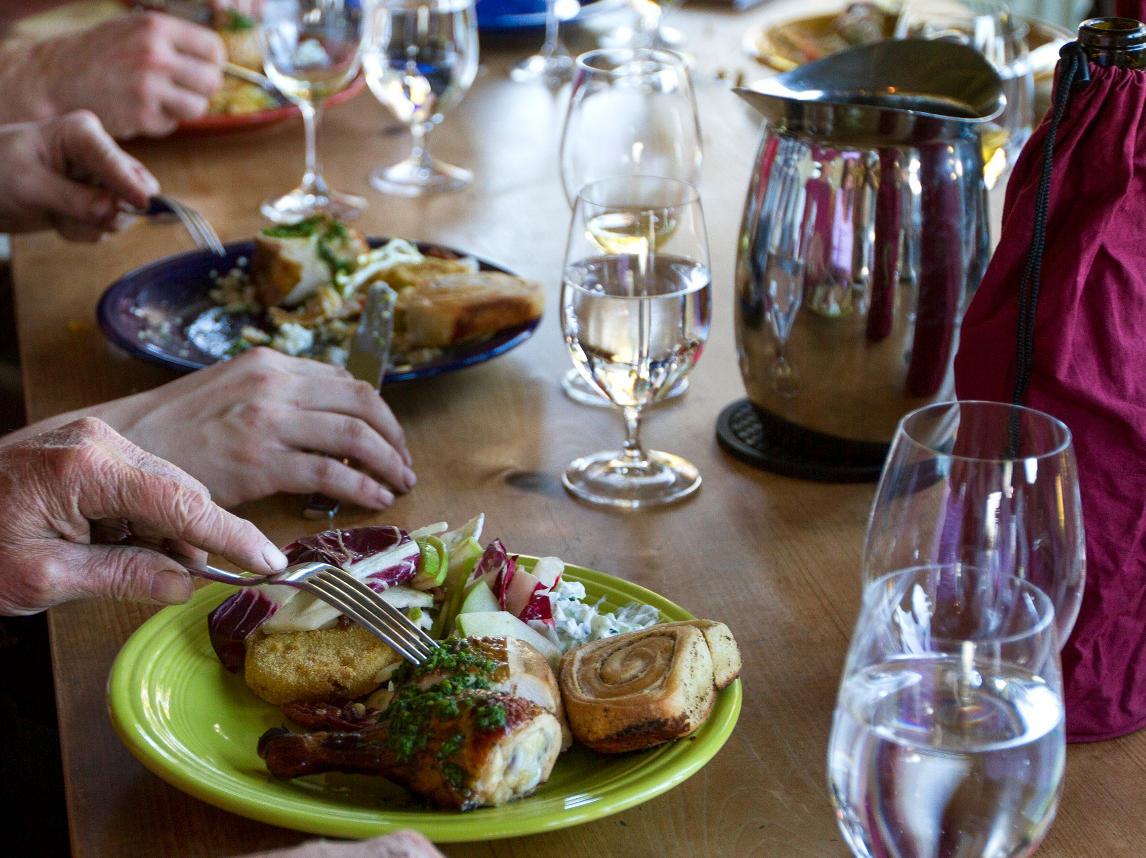 Cristom Winery vineyard workers enjoy a plate of chicken, salad, swirled buns and cardamom vanilla shortbread on Tuesday, Oct. 2, 2018. During harvest season Willamette Valley wineries will sometimes hire a chef to cook for a crew working 12-hour days.