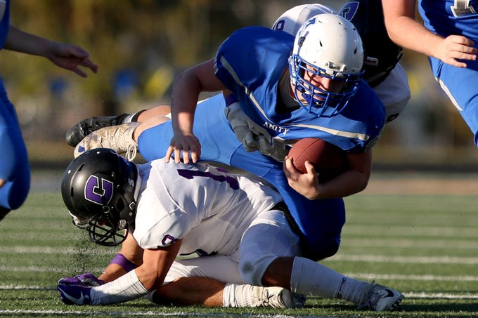 Amity's West Streeter (20) is tackled during the OSAA 3A semifinal Amity vs Cascade Christian football game on Saturday, Nov. 17, 2018 in Cottage Grove.