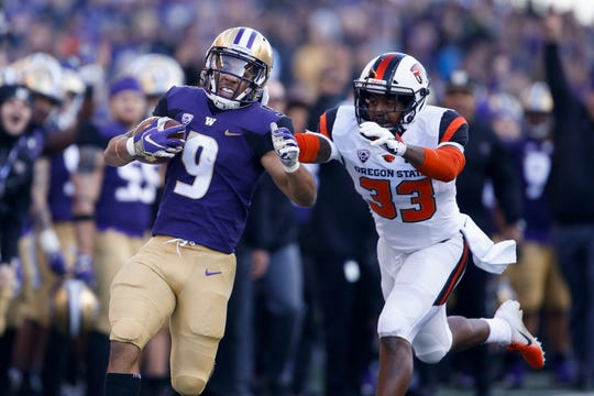 Nov 17, 2018; Seattle, WA, USA; Washington Huskies running back Myles Gaskin (9) moves the ball against Oregon State Beavers safety Jalen Moore (33) during the first quarter at Husky Stadium. Mandatory Credit: Jennifer Buchanan-USA TODAY Sports