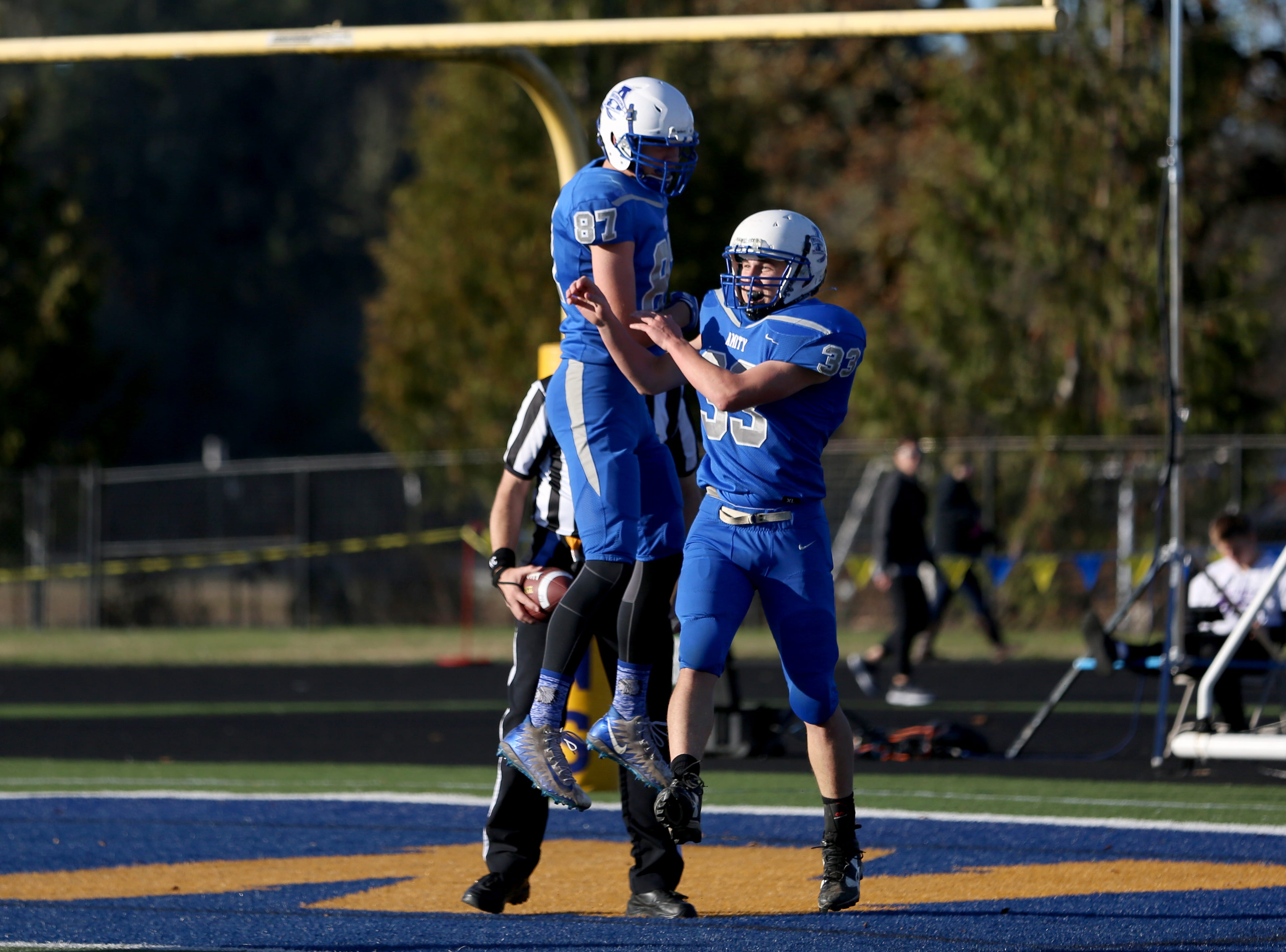 Amity's Josh Wart (87) and Jonathan Mather (33) celebrate after Mather's 72-yard touchdown during the OSAA 3A semifinal Amity vs Cascade Christian football game on Saturday, Nov. 17, 2018 in Cottage Grove.