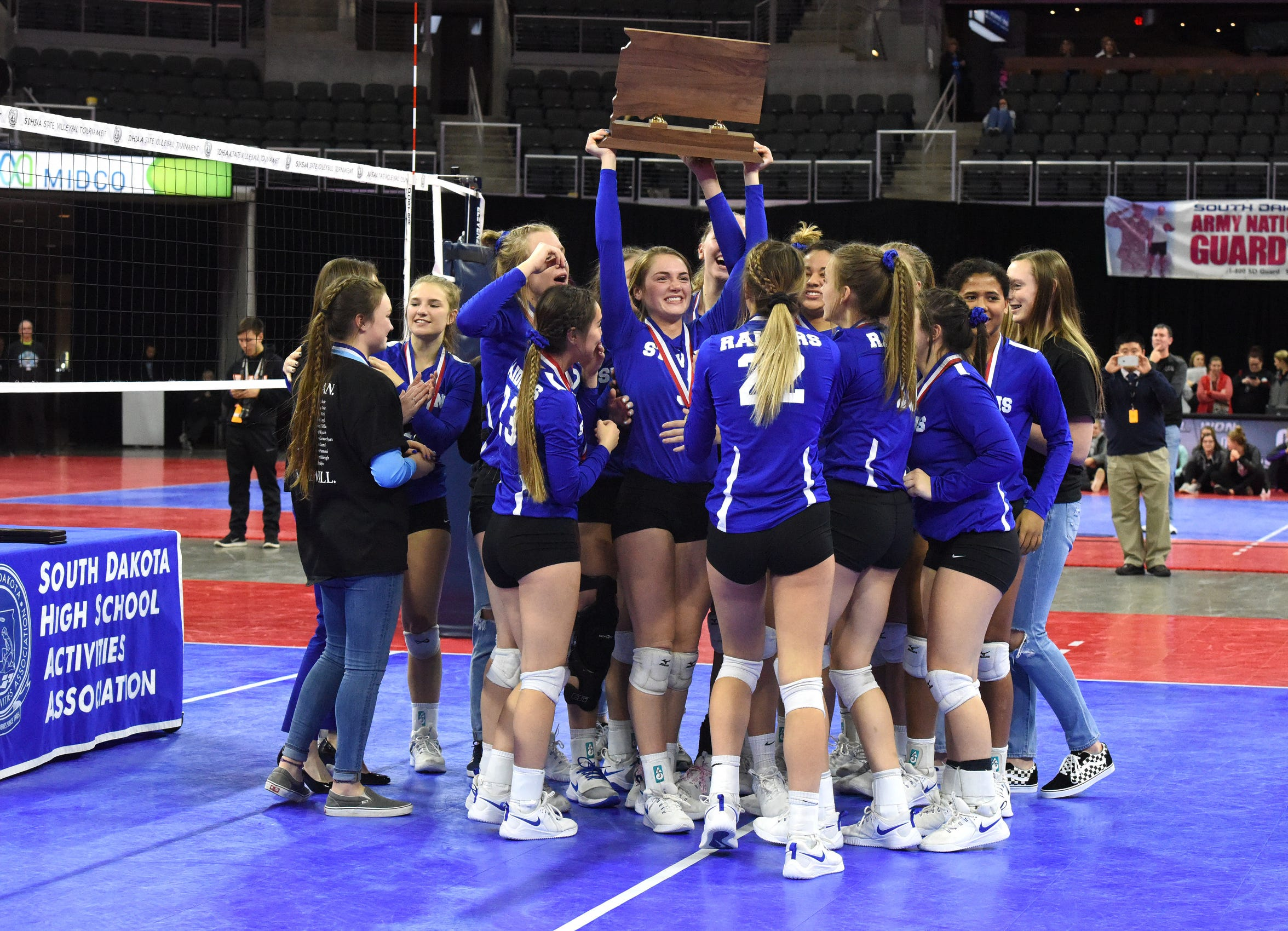 Rapid City Stevens senior Elizabeth Schaefer (center) holds up the Class AA state championship trophy as she celebrates with her teammates.